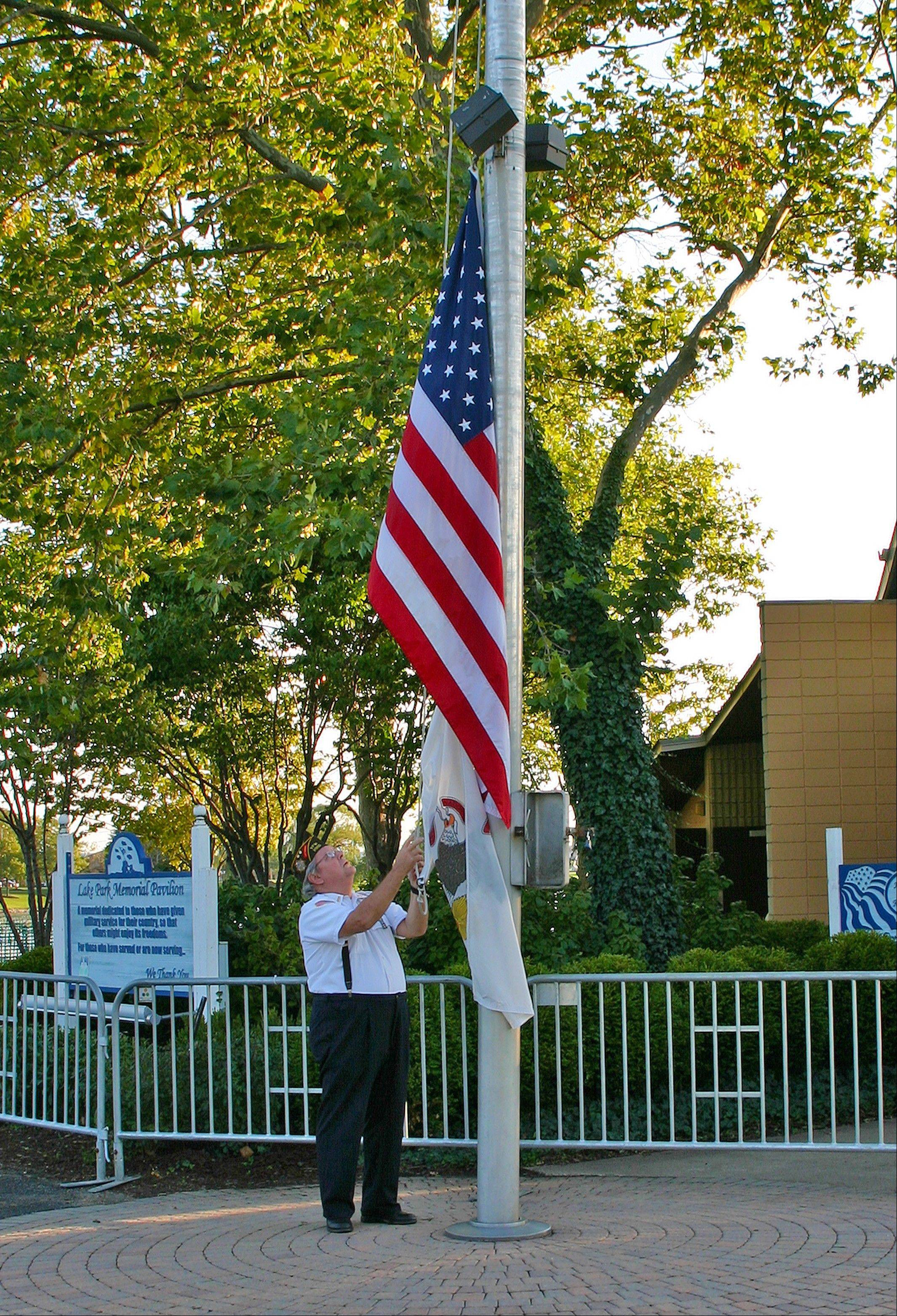 "Mike Lake, VFW Post 2992, raises the flag to kick off Fall Fest 2012 in Des Plaines. The flag was raised Friday evening for the ""Pledge of Allegiance"" and then lowered to half-mast in honor of Libyan Ambassador Christopher Stevens and his staff. Stevens was killed in an attack Sept. 11."