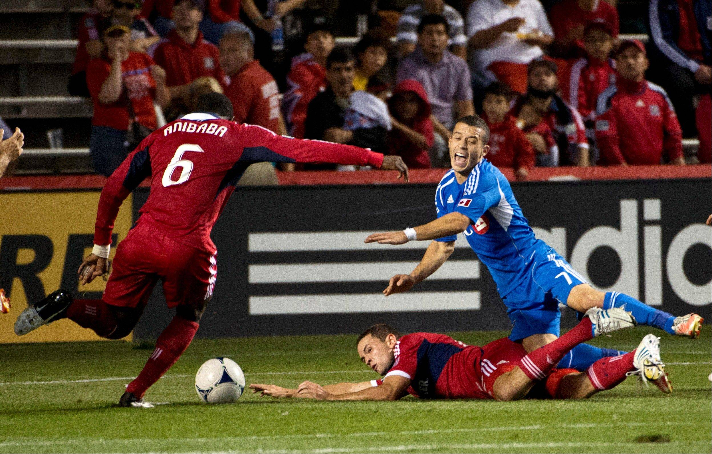 Montreal Impact midfielder Felipe Martins, right, is tripped by Chicago Fire defender Austin Berry, center, as defender Jalil Anibaba goes for the ball Saturday in Bridgeview.