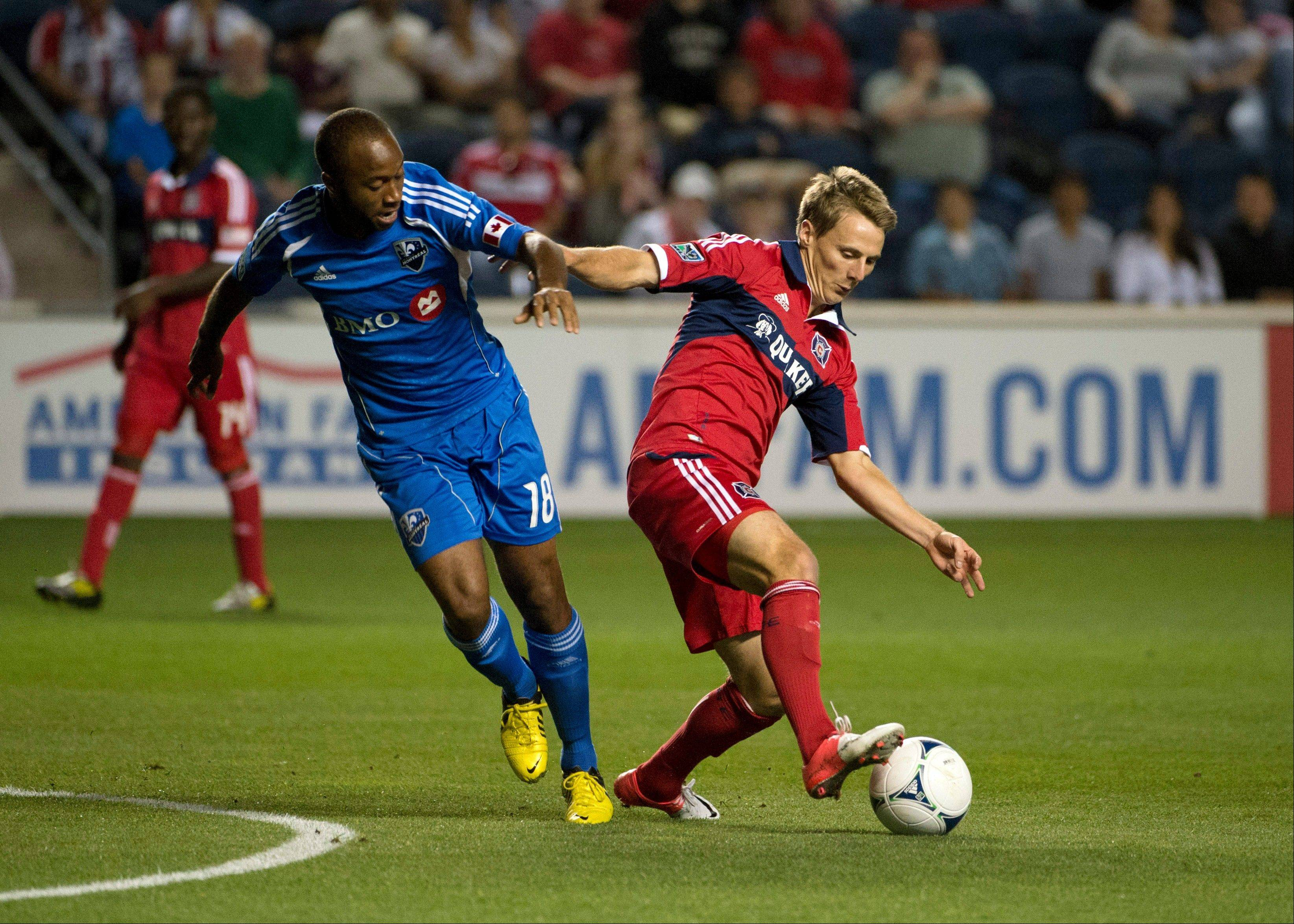 Montreal Impact midfielder Collen Warner, left, and Chicago Fire forward Chris Rolfe vie for the ball during the first half of a soccer match, Saturday, Sept. 15, 2012 in Bridgeview, Ill.