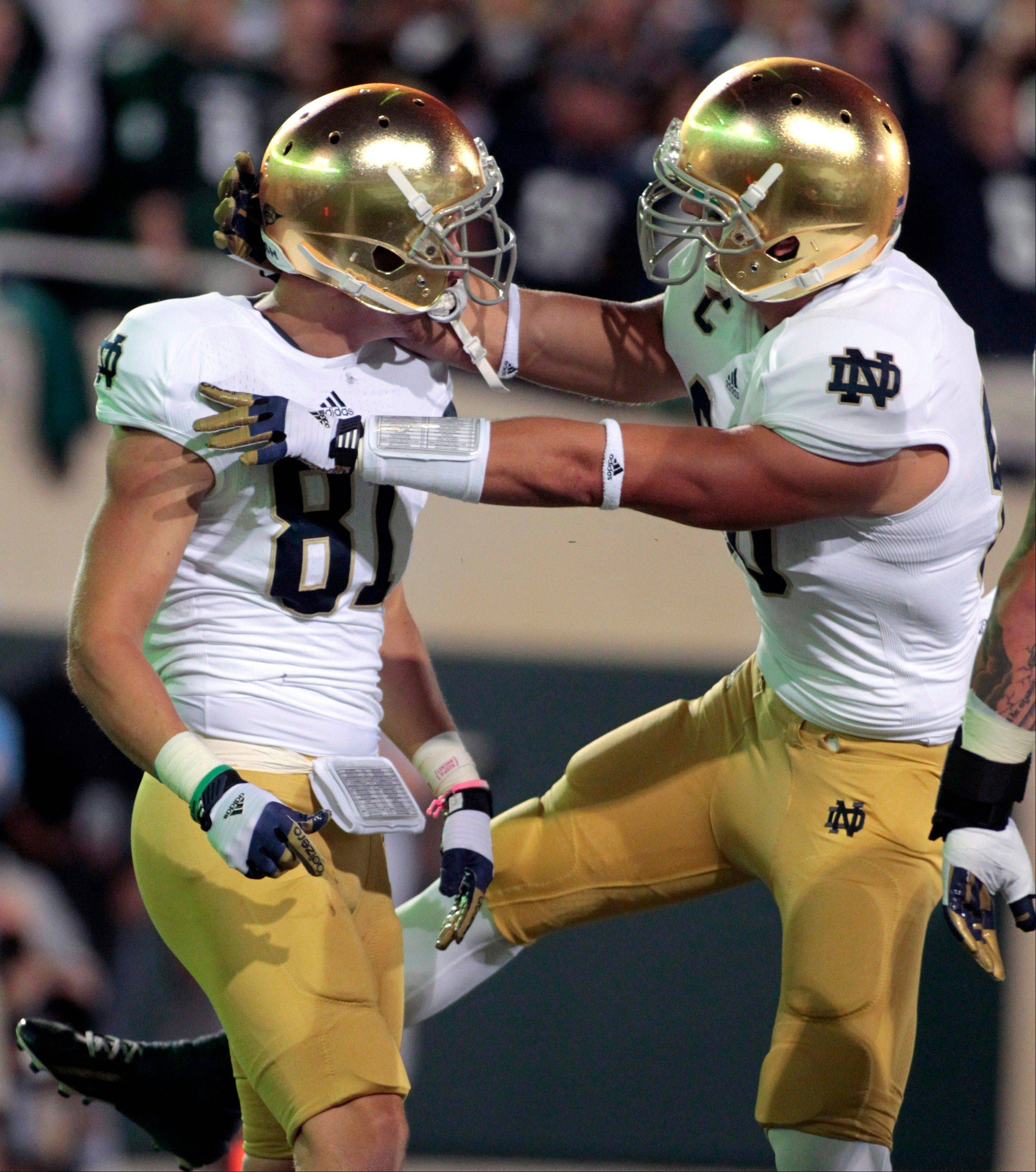 Notre Dame's John Goodman, left, and Tyler Eifert celebrate Goodman's touchdown reception during the first quarter of an NCAA college football game against Michigan State, Saturday, Sept. 15, 2012, in East Lansing, Mich.