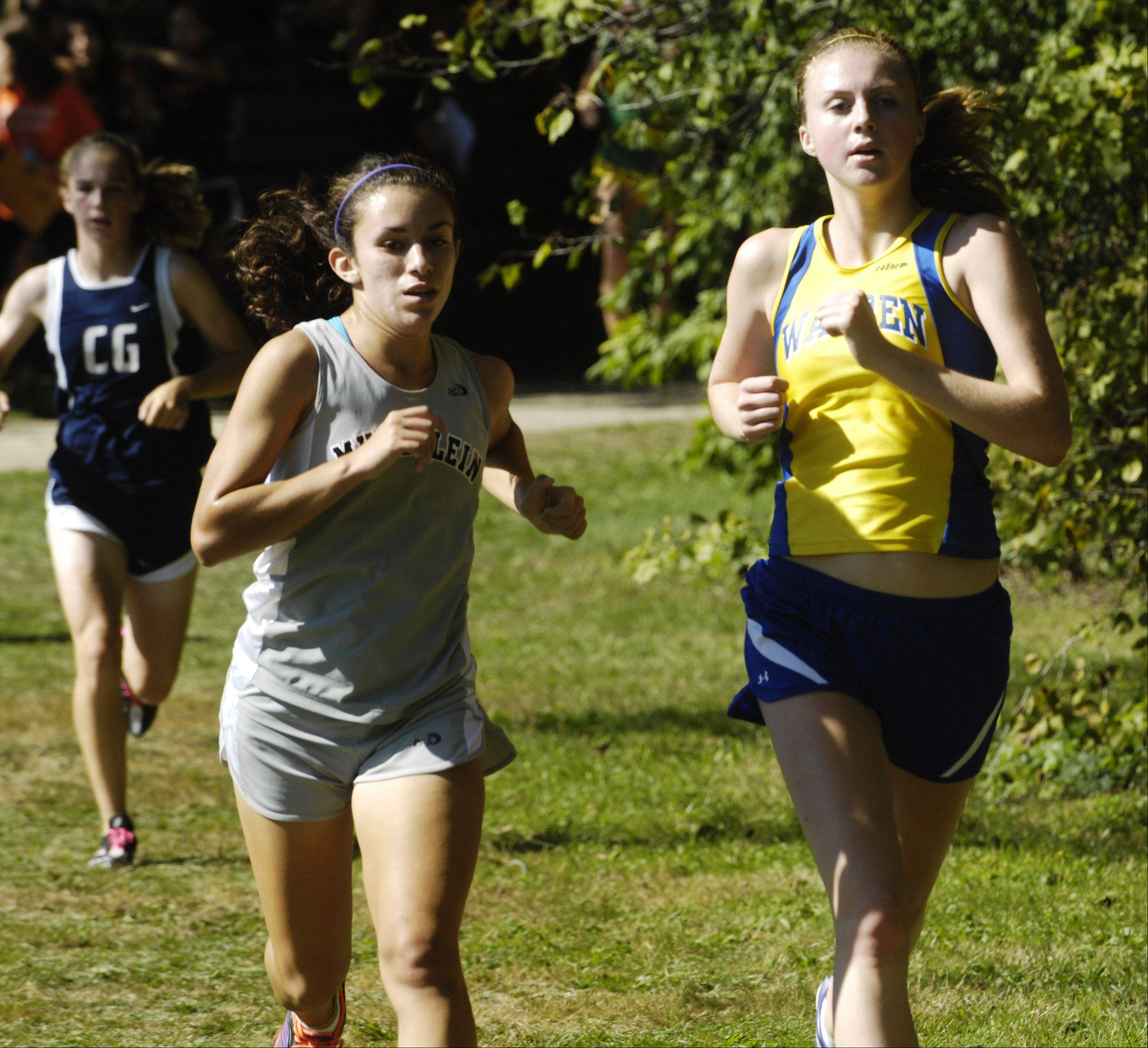 Mundelein's Elena Palacios, left, and Warren's Meg Tully run alongside one another during the Warren cross country invite in Gurnee on Saturday.