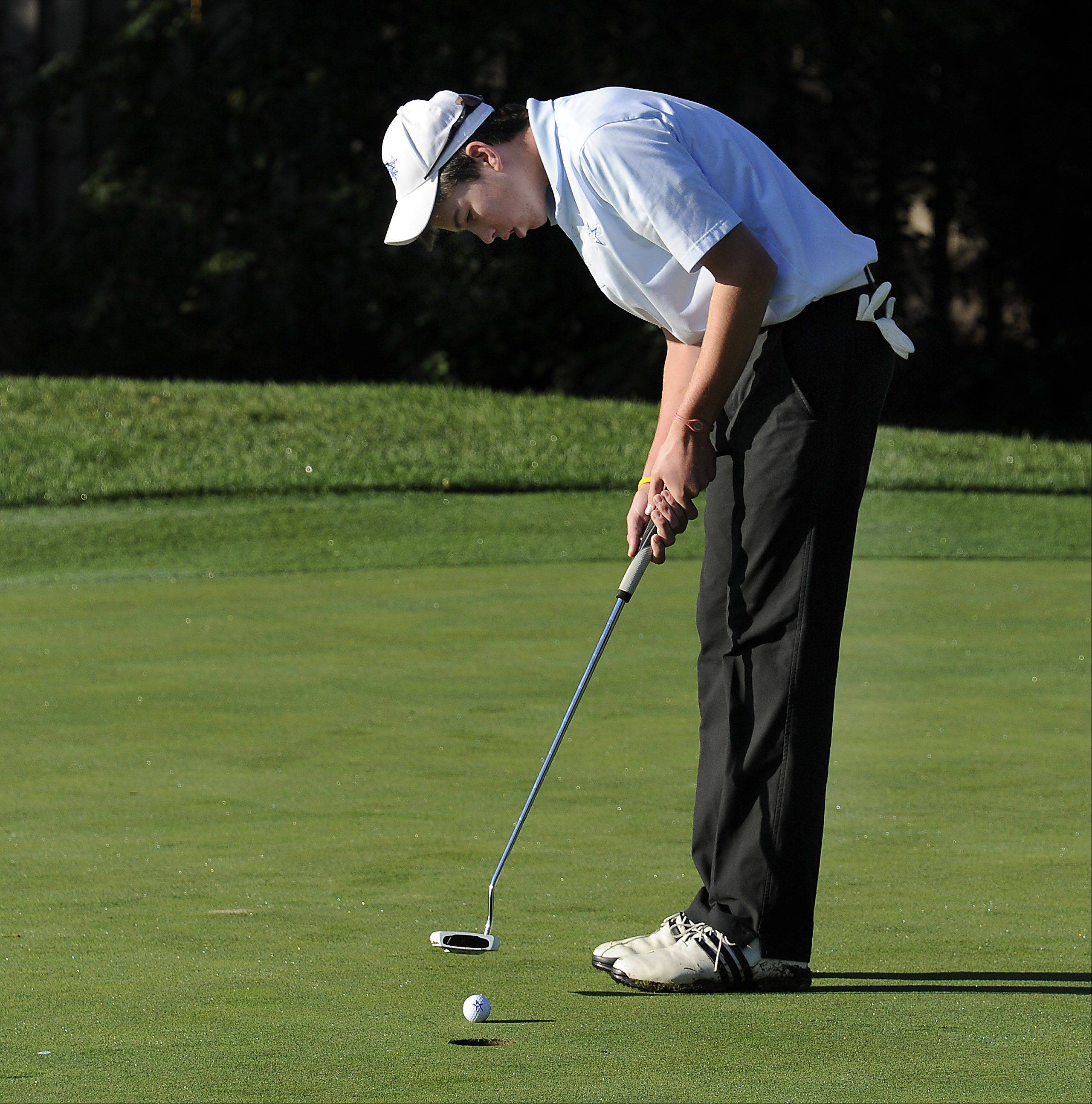 St. Charles North's Dan Sheperd taps in his short putt on the second hole at the Wheeling Invitational on Saturday.