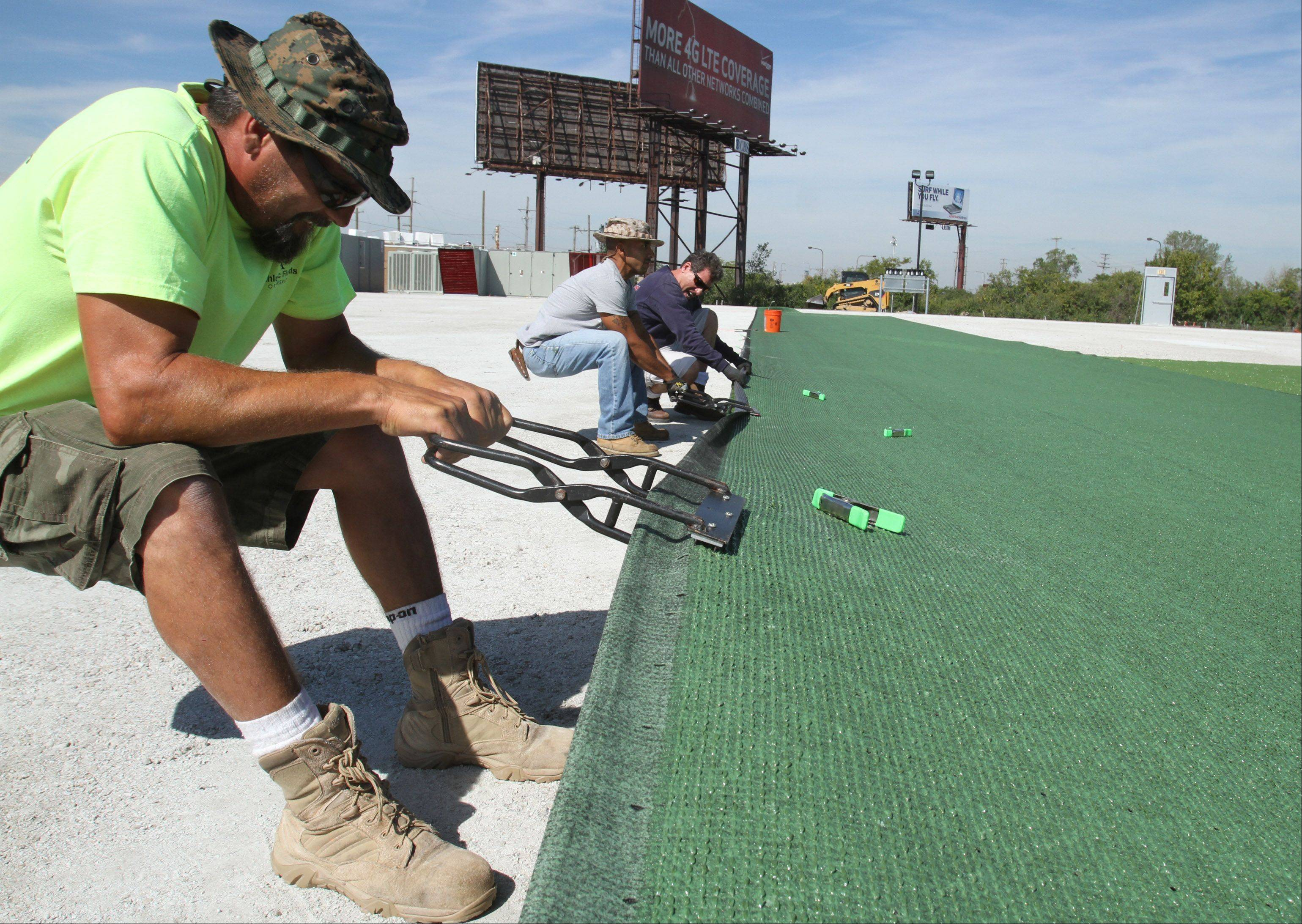 Steven Dills with Athletic Fields of America, foreground, pulls and stretches artificial turf Wednesday for a new indoor athletic training facility in Rosemont.
