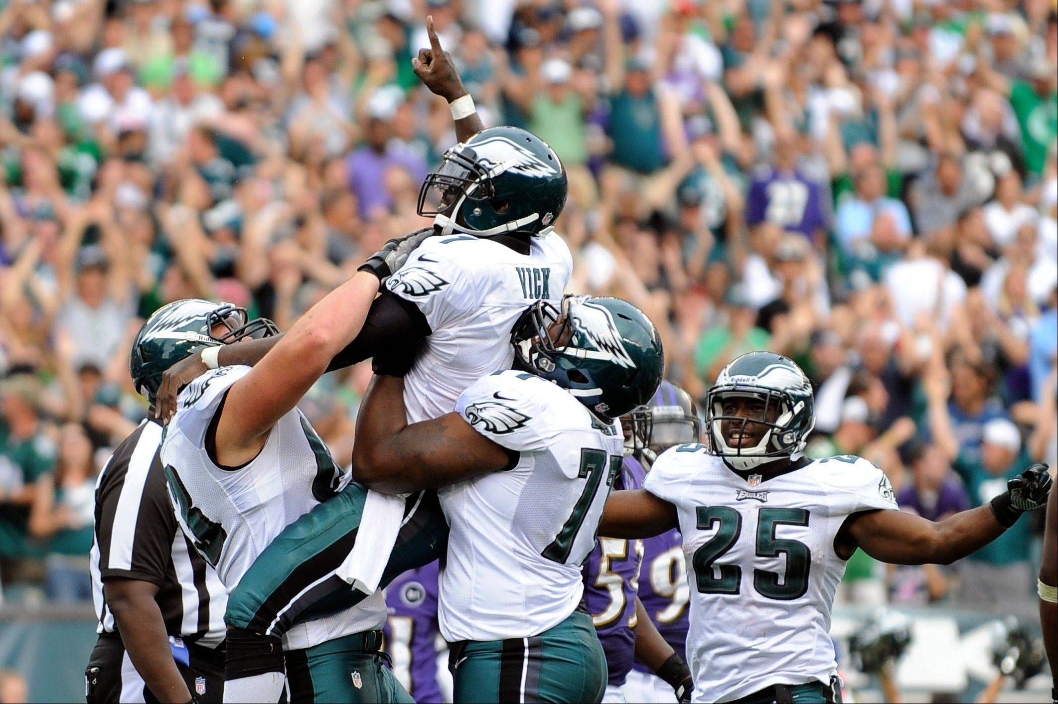 From left to right, Philadelphia Eagles� Danny Watkins, Michael Vick and Demetress Bell and LeSean McCoy celebrate after Vick�s rushing touchdown in the second half against the Baltimore Ravens.
