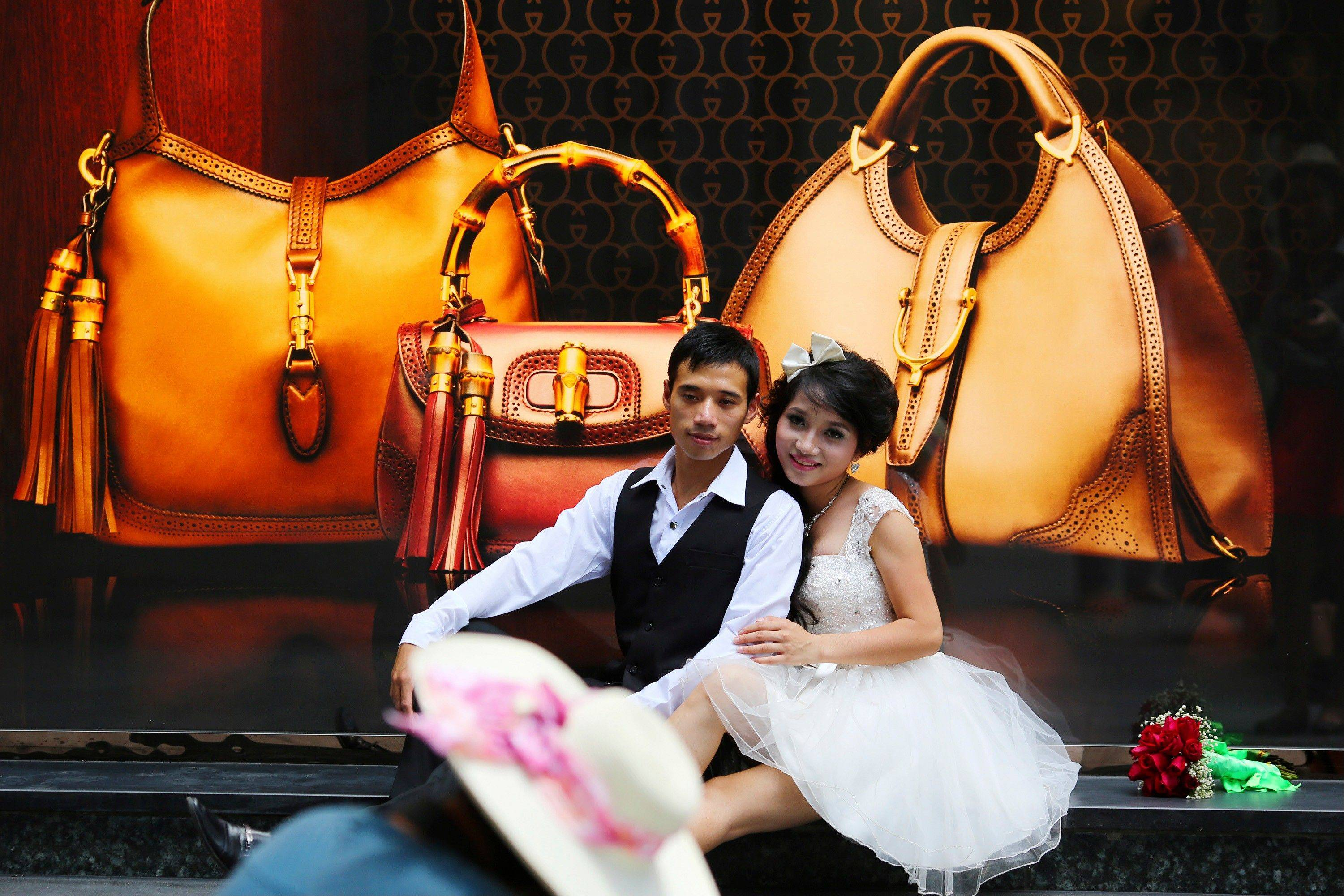A couple pose for photos in front of a luxury shop in Hanoi, Vietnam. Once seen as an emerging Asian dynamo racing to catch up with its neighbors, Vietnam's economy is mired in malaise, dragged down by debt-hobbled banks, inefficient and corrupt state-owned enterprises and bouts of inflation.