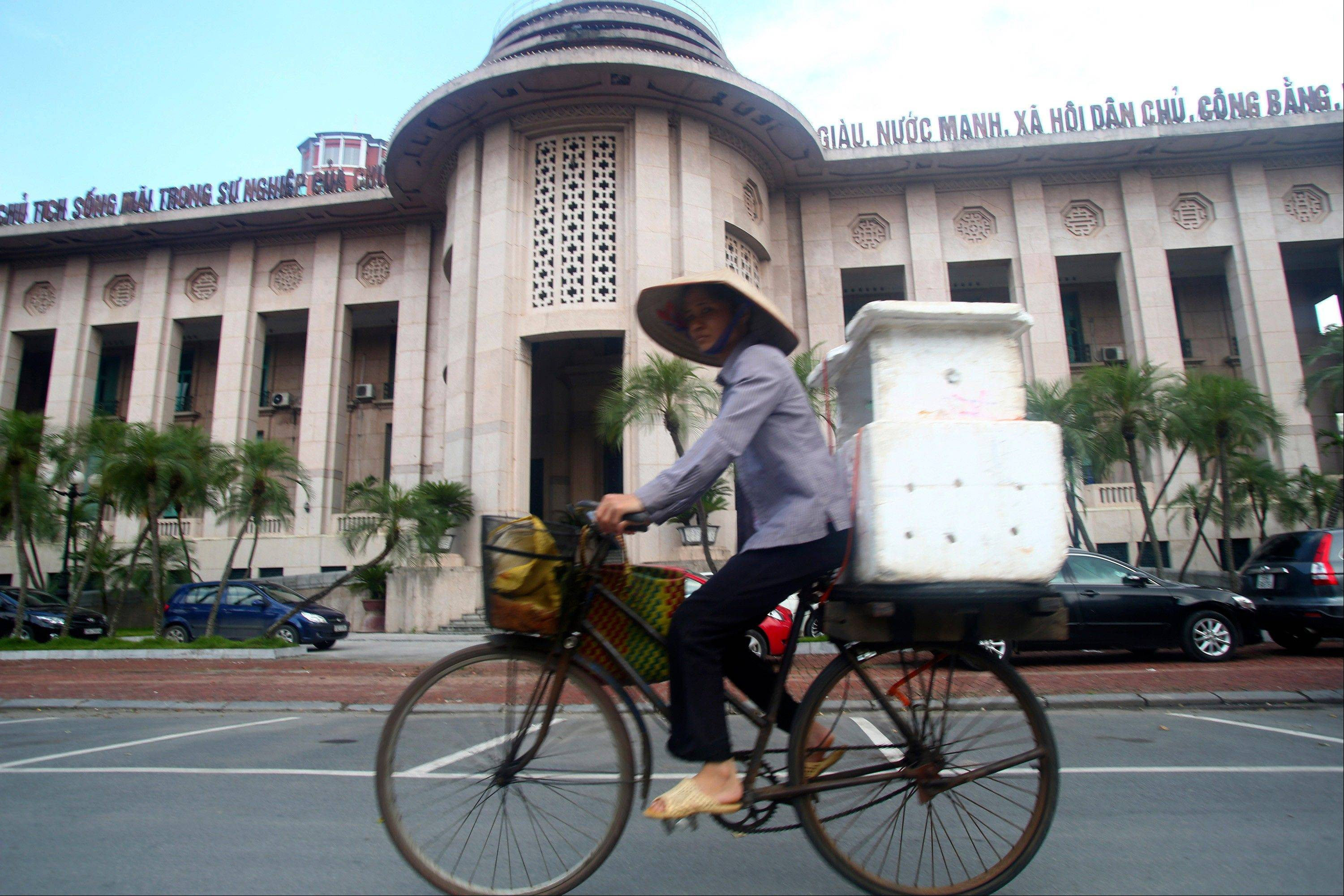 A street vendor cycles past the Central Bank of Vietnam in Hanoi, Vietnam. Once seen as an emerging Asian dynamo racing to catch up with its neighbors, Vietnam's economy is mired in malaise, dragged down by debt-hobbled banks, inefficient and corrupt state-owned enterprises and bouts of inflation.
