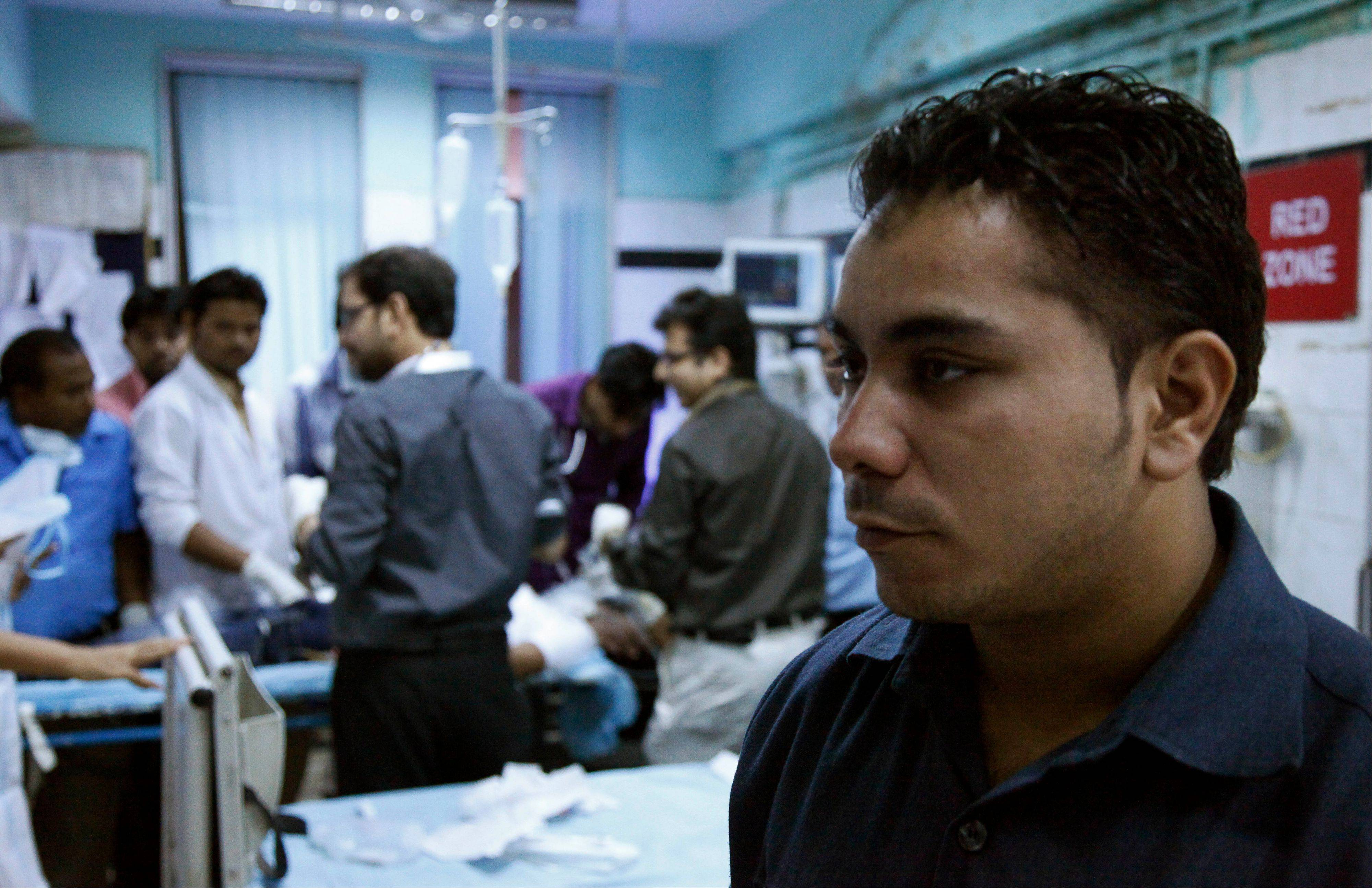 Amarjeet Singh, right, stands guard inside the emergency room at the Deen Dayal Upadhyay Hospital in New Delhi, India.