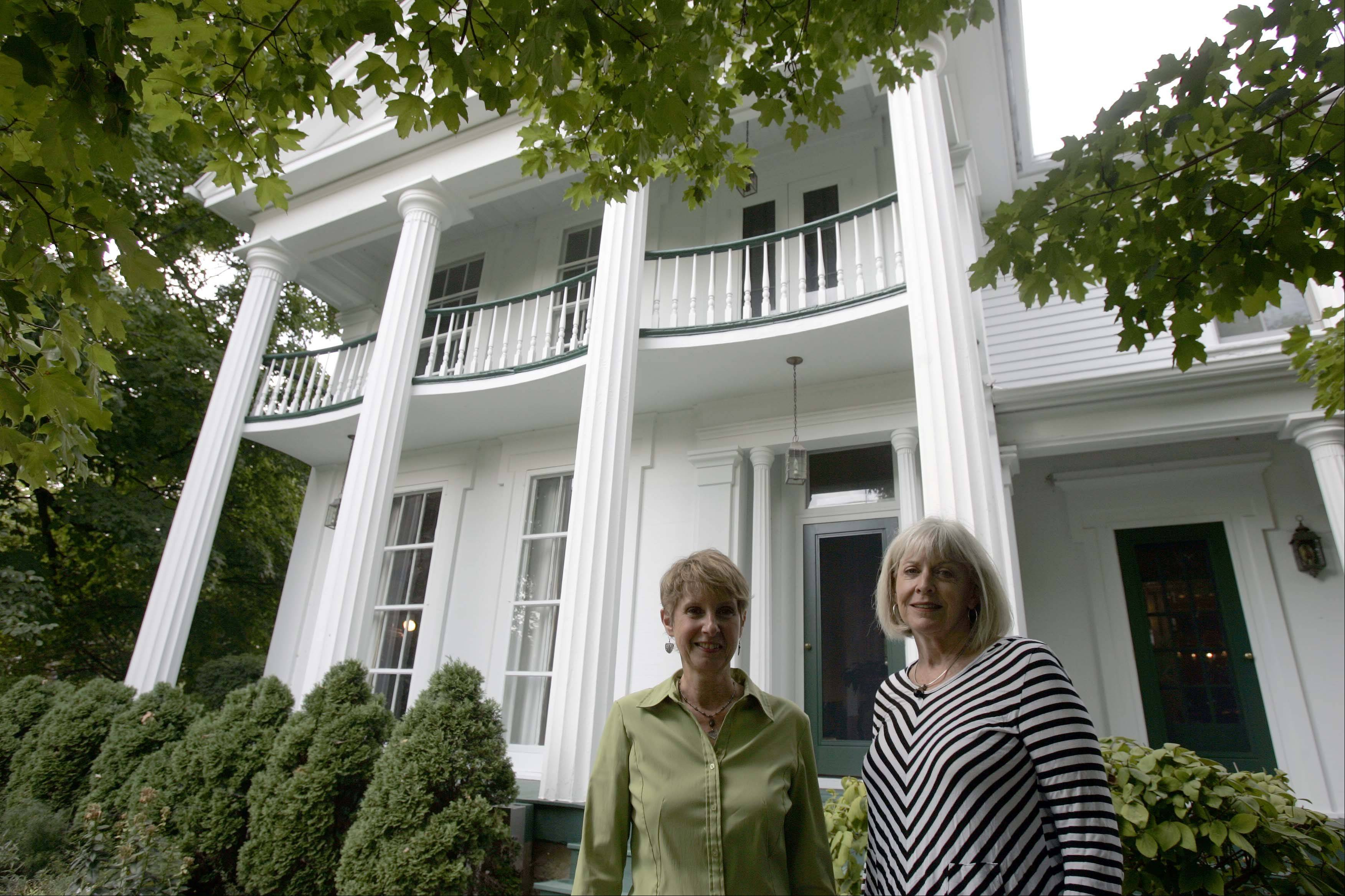 Tour guides Linda Winans, left, and Pat Pretz, both of St. Charles, outside the 1859 home built for two-time Mayor Dr. James Lewis on Fifth Street in St. Charles. The home is one of the most elegant examples of Greek Revival architecture on the tour.