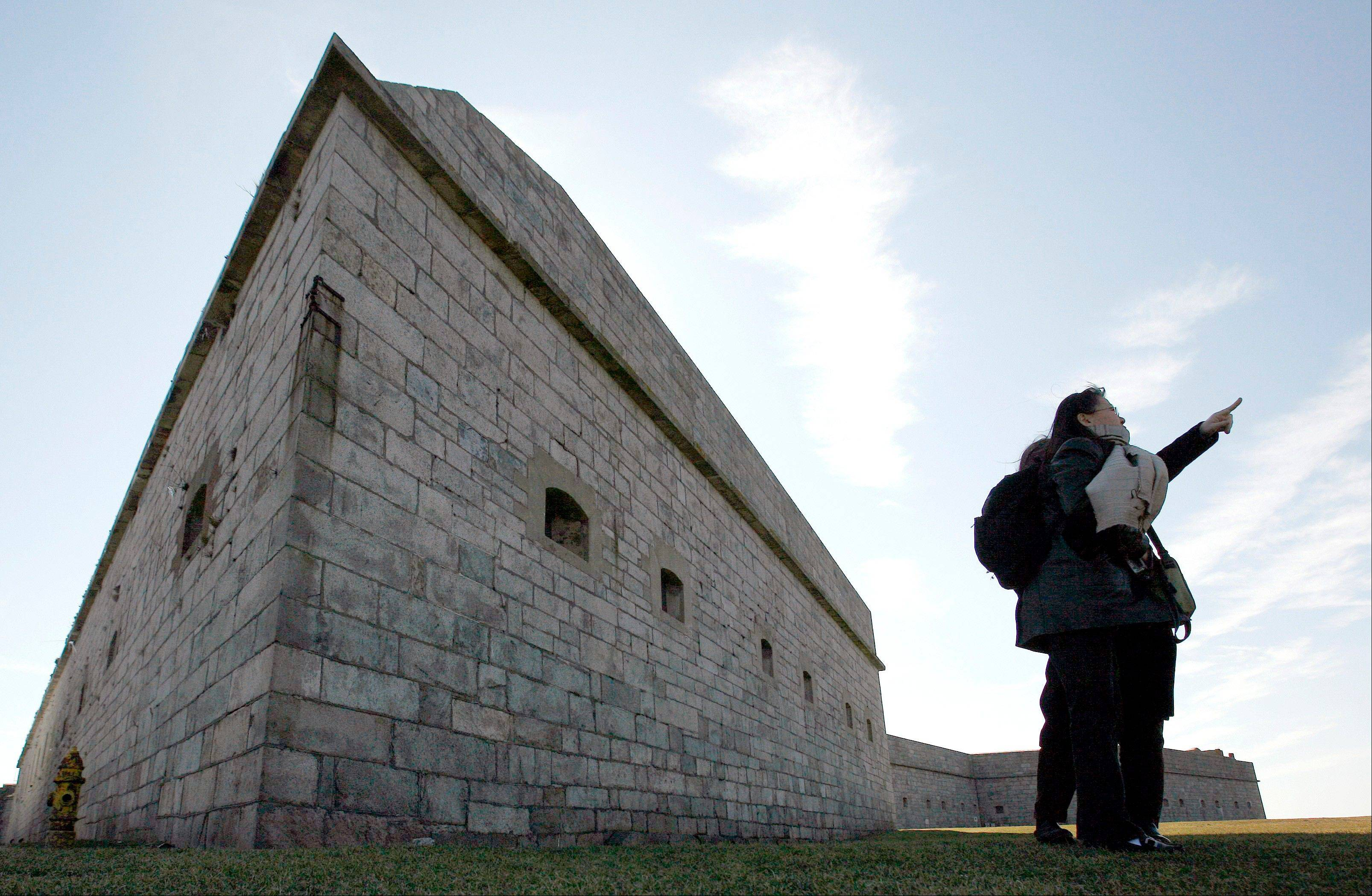 The walls of Fort Adams loom behind visitors at the site in Newport, R.I.