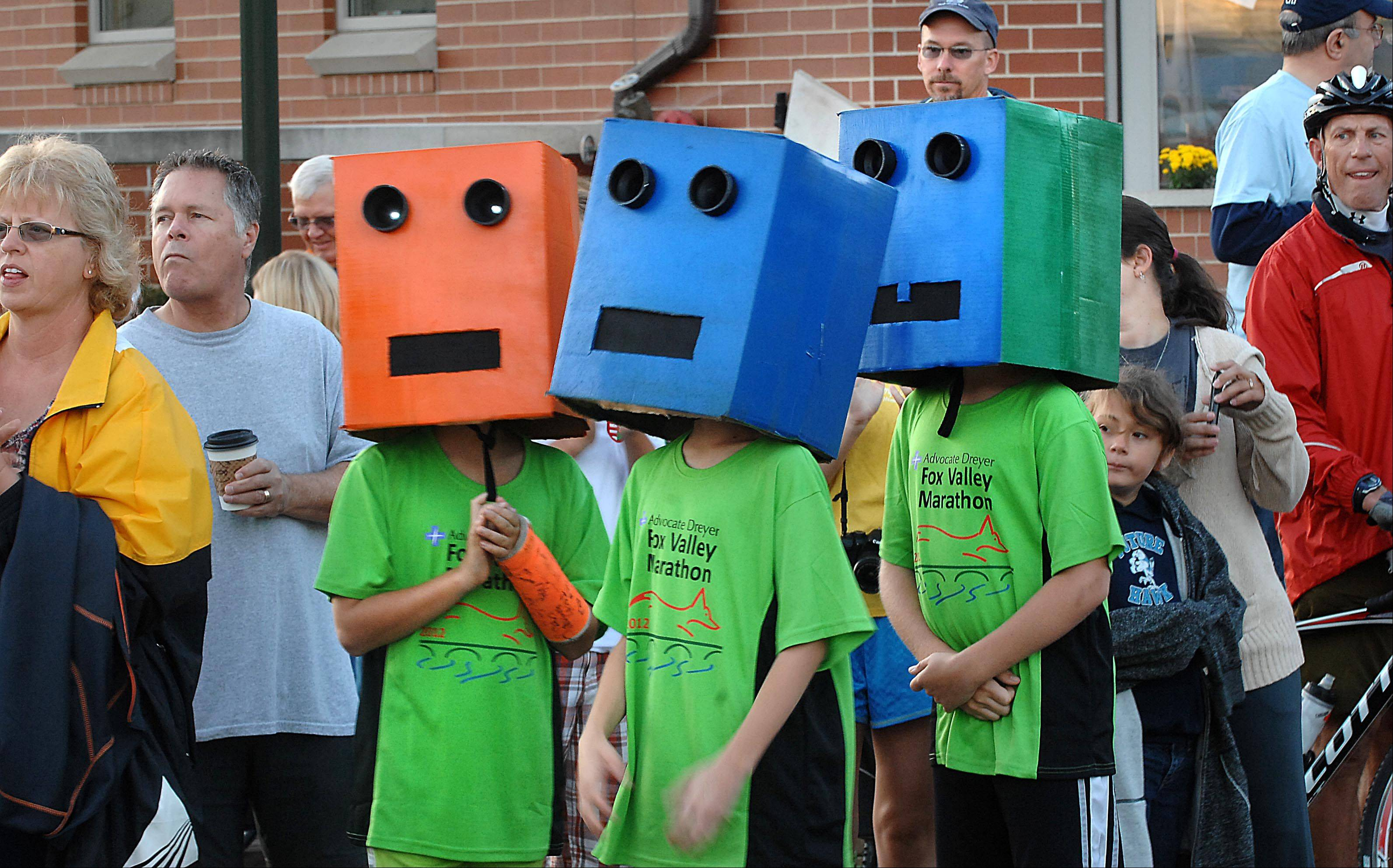 Matthew Fuller, 10, Hank Smith, 11, and Nathan Hilkenann, 10, wore painted boxes with lighted eyes on First Street in St. Charles Sunday morning at the start of the Fox Valley Marathon. The top 30 finishers qualified for the prestigious Boston Marathon. There was also a half marathon and a Final Fall 20-mile race.