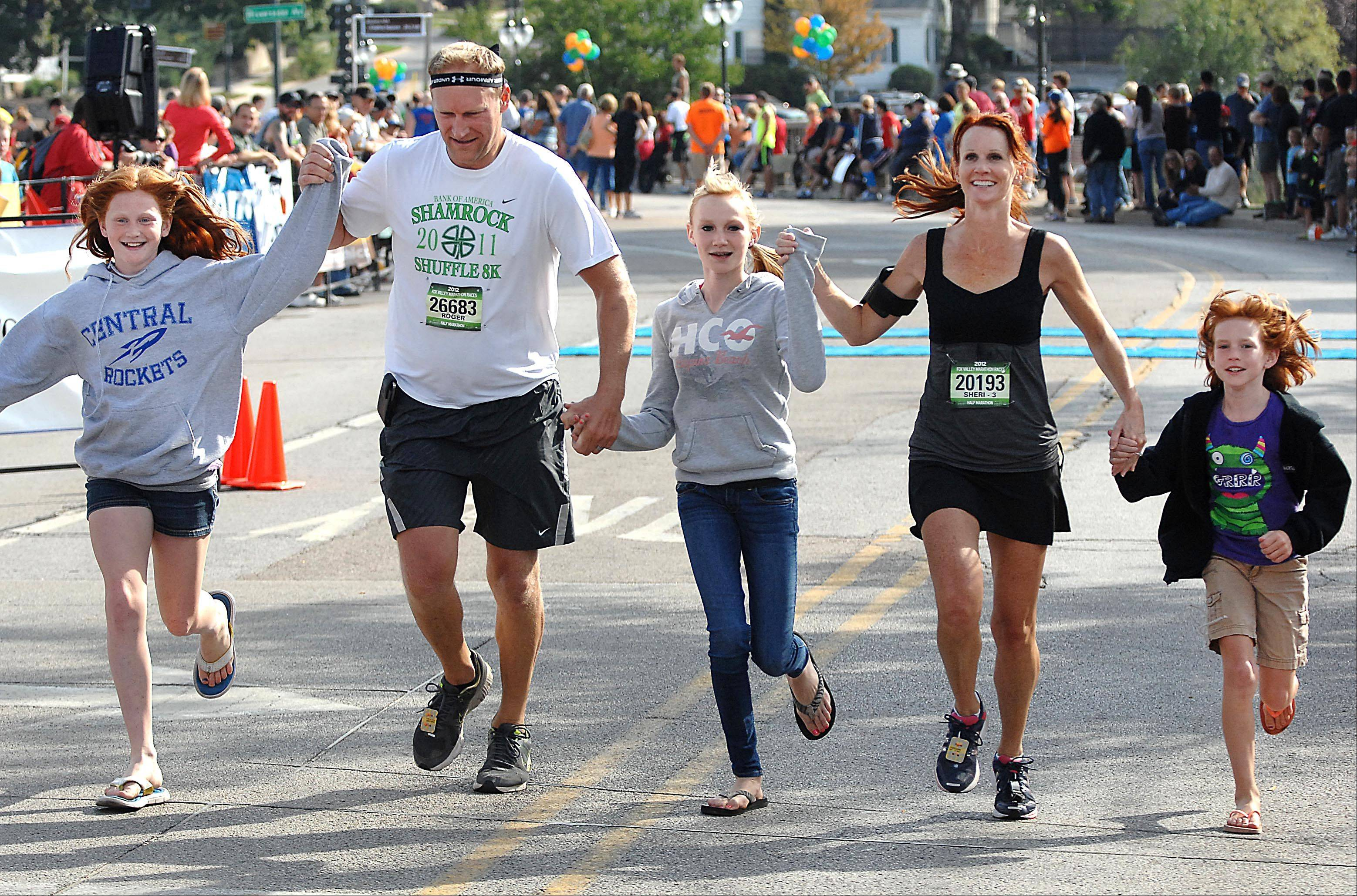 Roger and Sheri Greenhagel of Elgin finish the Fox Valley Half Marathon with their children, Paige, Emily and Brin, joining them for the last few yards Sunday in St. Charles.
