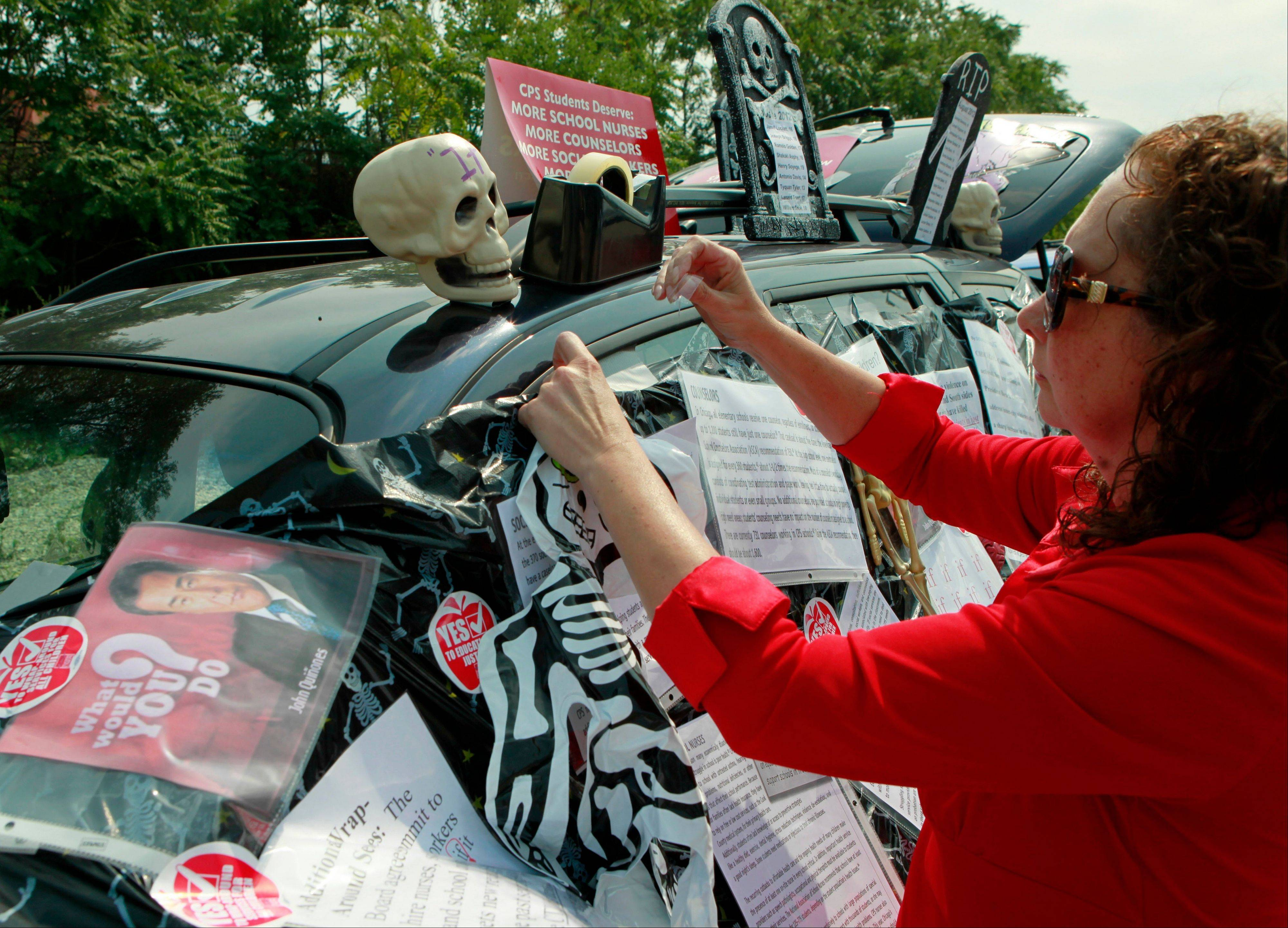 Philomena Johnson, a delegate from Little Village Academy, decorates her vehicle Sunday to highlight the need for increased social services in schools before attending a meeting of the Chicago Teachers Union delegates.