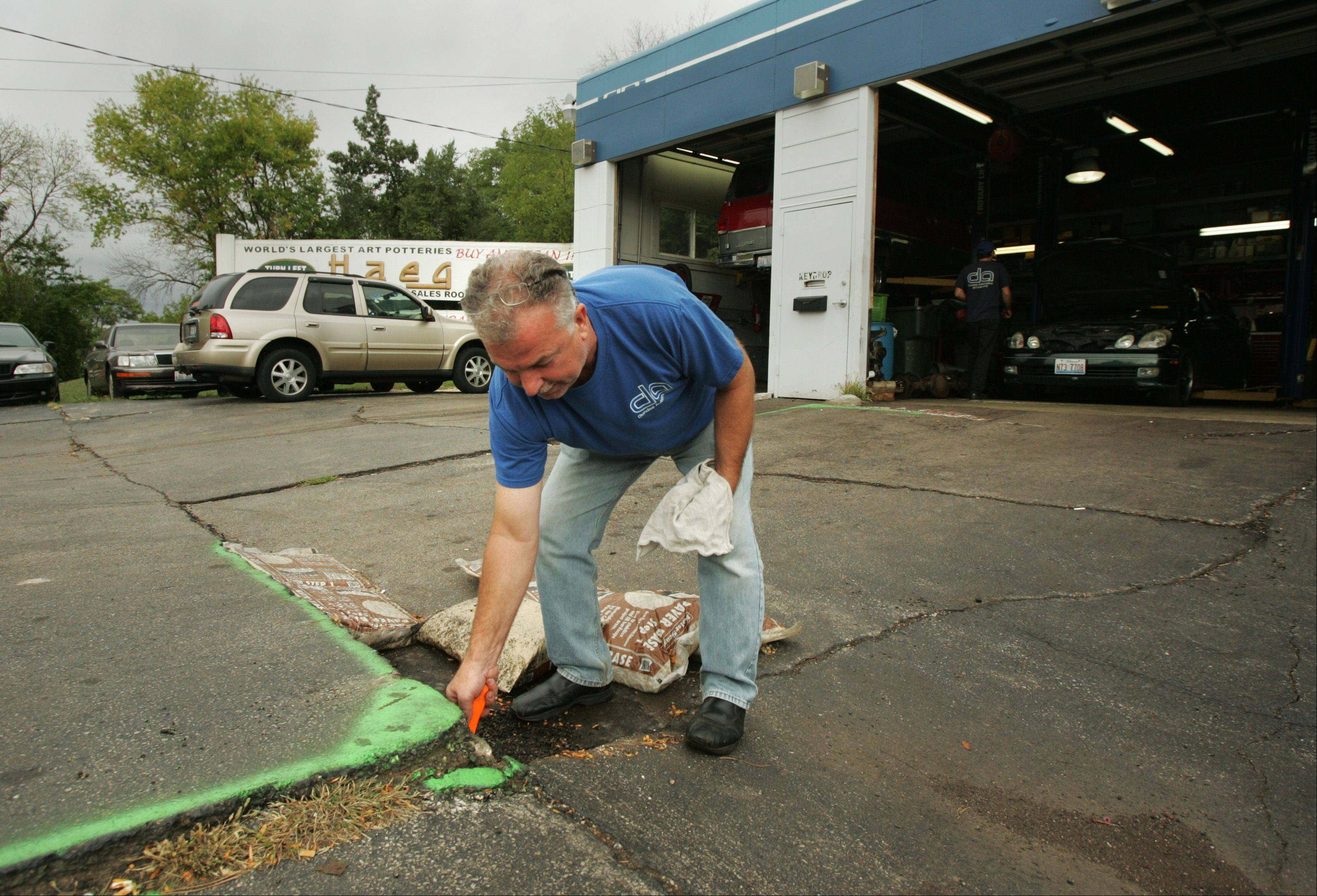 Dundee Automotive owner Randy Klemm believes that a broken water pipe beneath the parking lot in front of the East Dundee business is causing the parking lot to collapse. Here, Klemm pokes a screwdriver, which is more than a foot long, into a hole beneath the buckling asphalt.