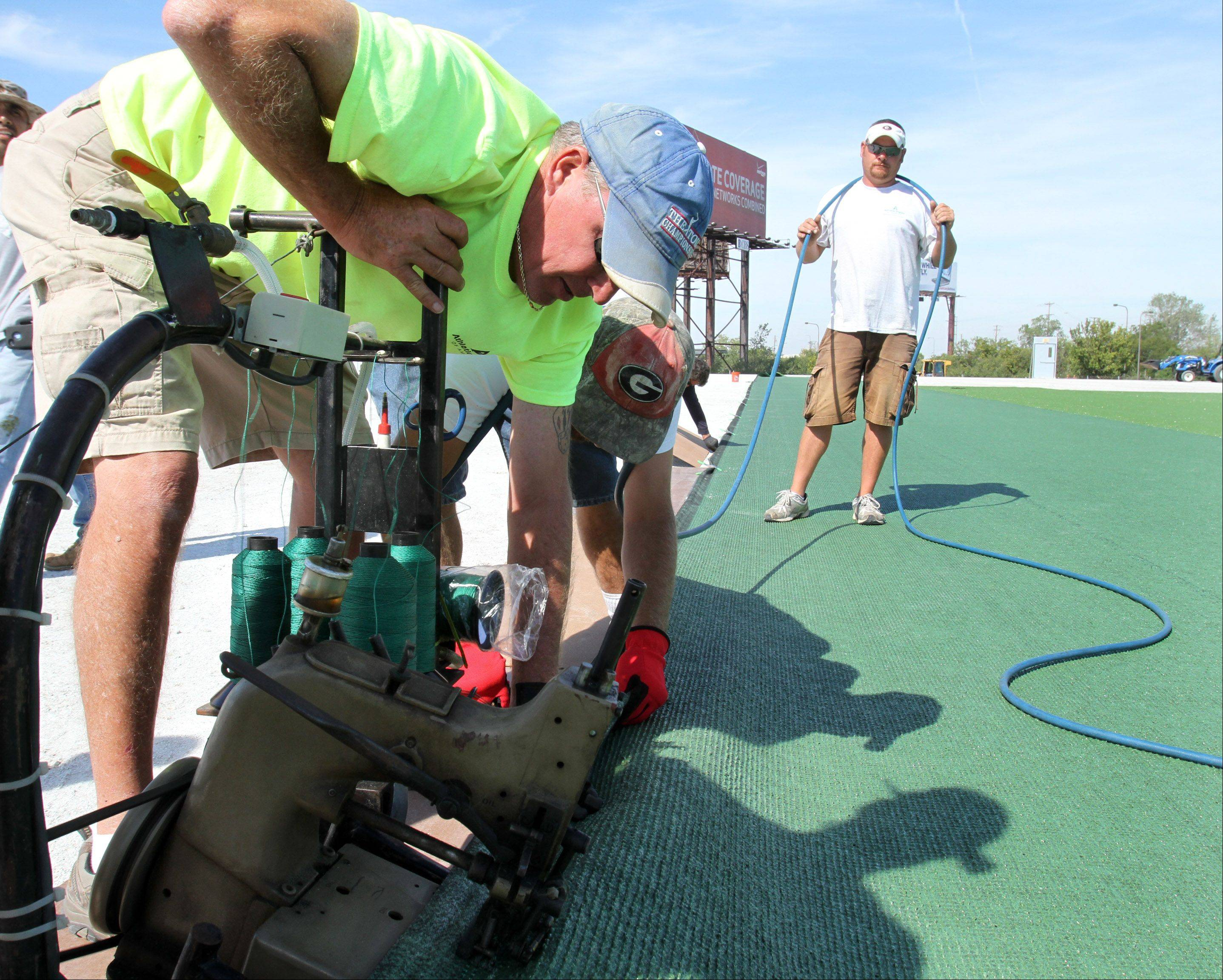 Jrone Jones with Athletic Fields of America, foreground, uses a sewing machine on a cart to stitch an artificial turf covering the ground for a new seven-story dome for an indoor athletic training facility in Rosemont.