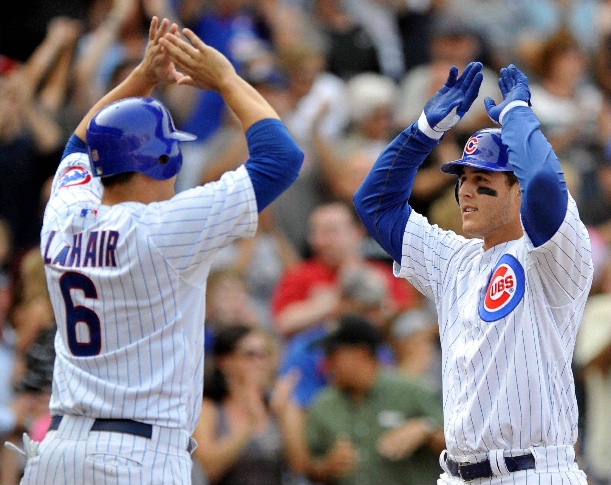 The Cubs' Anthony Rizzo celebrates with Bryan LaHair at home plate Sunday after hitting his first career grand slam.