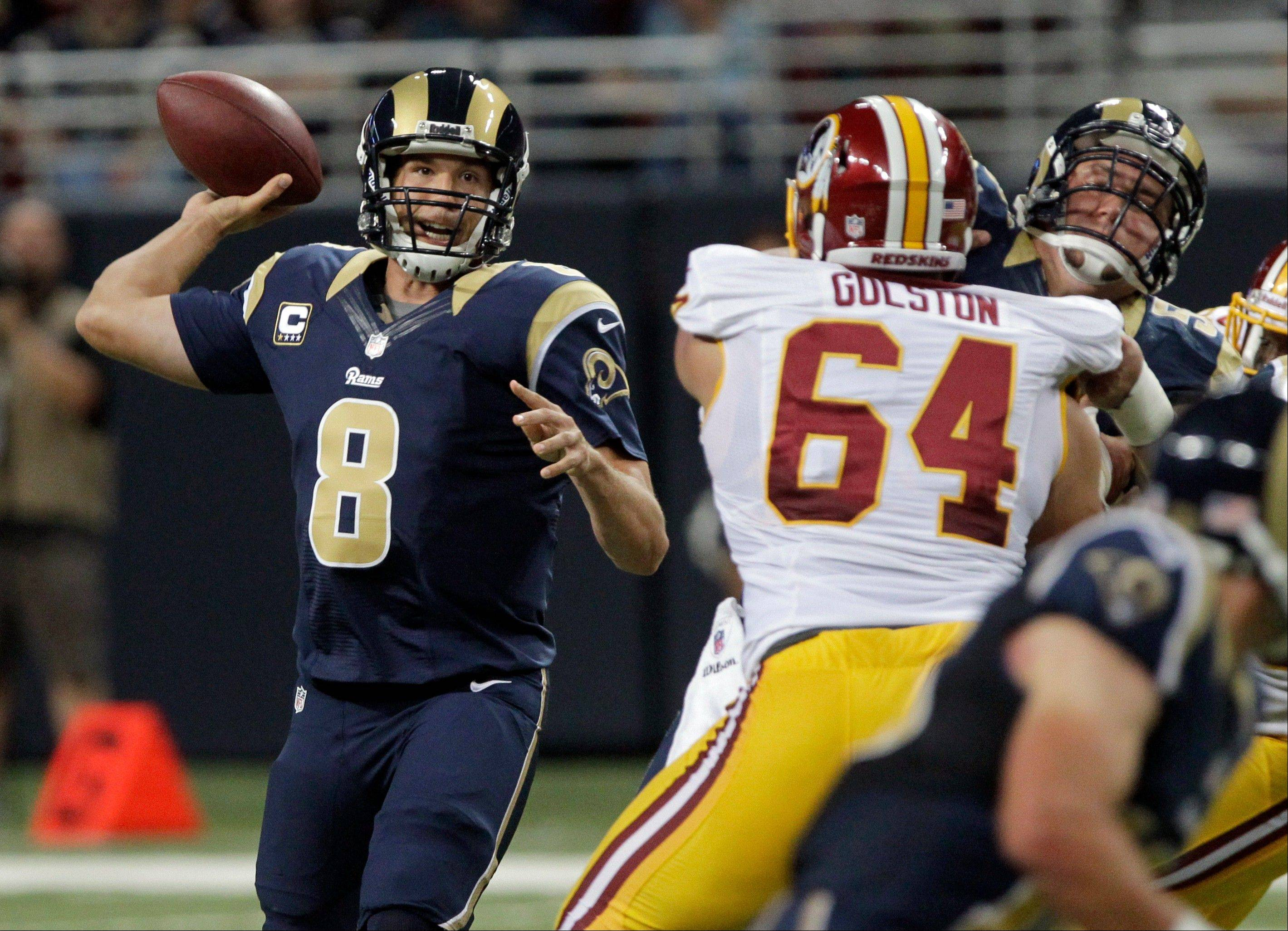 St. Louis Rams quarterback Sam Bradford, left, throws during the first quarter of an NFL football game against the Washington Redskins, Sunday, Sept. 16, 2012, in St. Louis.
