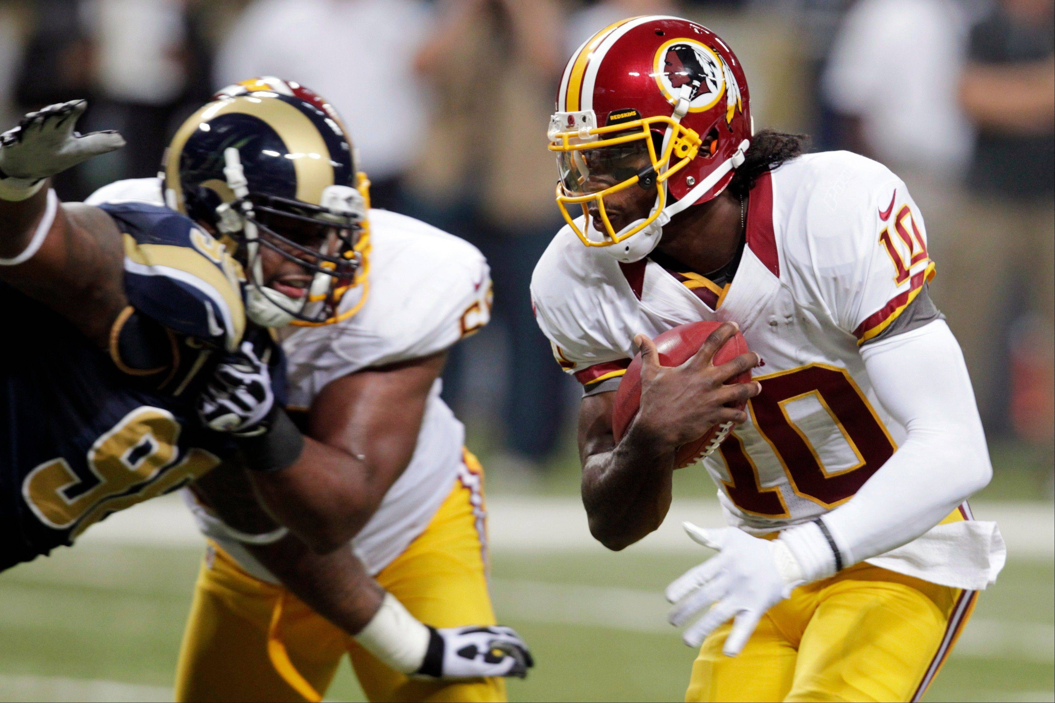 Robert Griffin III (10) runs past Rams defensive tackle Kendall Langford on his way to a touchdown Sunday. Griffin and the Redskins didn't win Sunday, but they did rack up 176 yards on the ground. Rookie running back Alfred Morris had 89 on 16 carries.