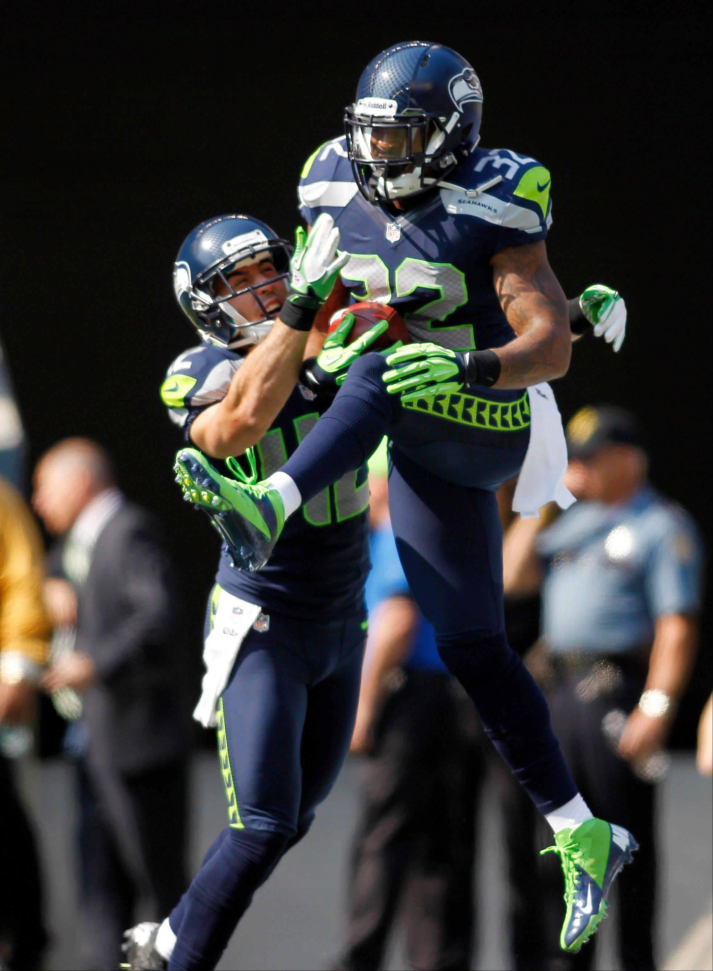 Seattle Seahawks' Jeron Johnson, right, celebrates his touchdown with Chris Maragos against the Dallas Cowboys in the first half of an NFL football game on Sunday.