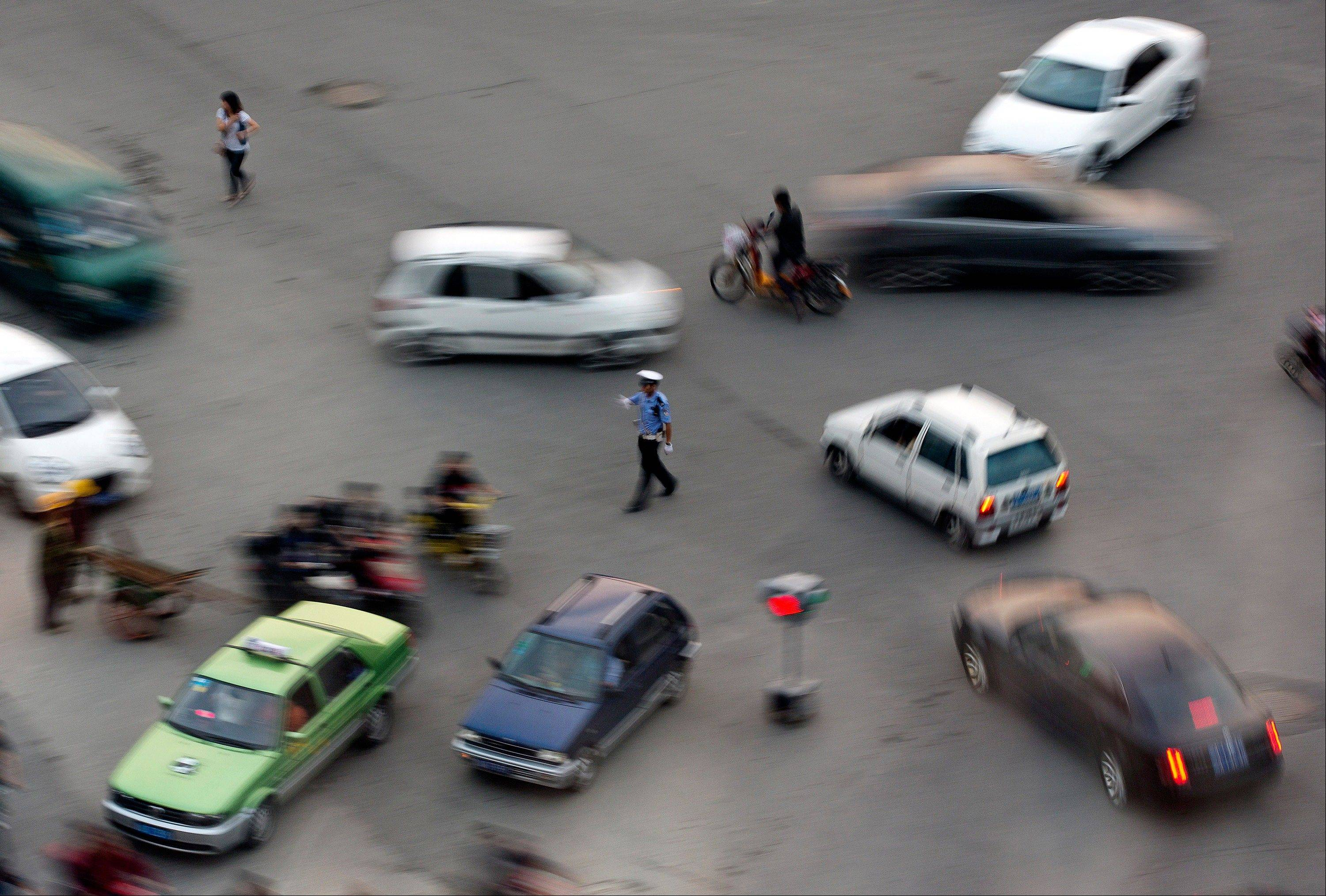 A Chinese policeman directs traffic at a road junction in Chengdu in southwest China�s Sichuan province Monday.