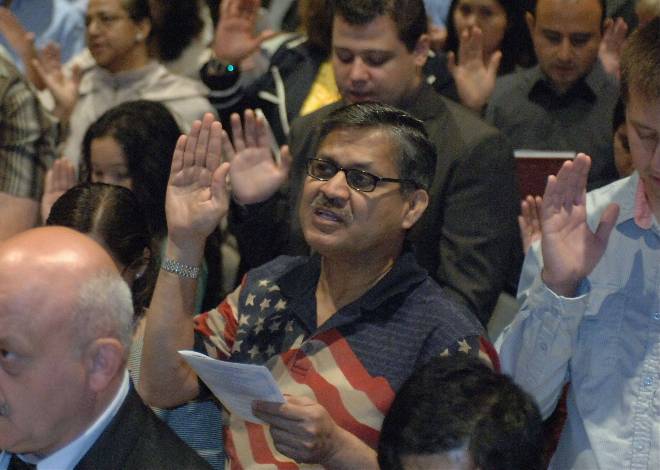 Basith Meer of Lincolnshire takes the Oath of Allegiance during a naturalization ceremony Monday at the Round Lake Beach Cultural & Civic Center. Mano a Mano Family Resource Center in partnership with the Round Lake Area Public Library hosted the event.