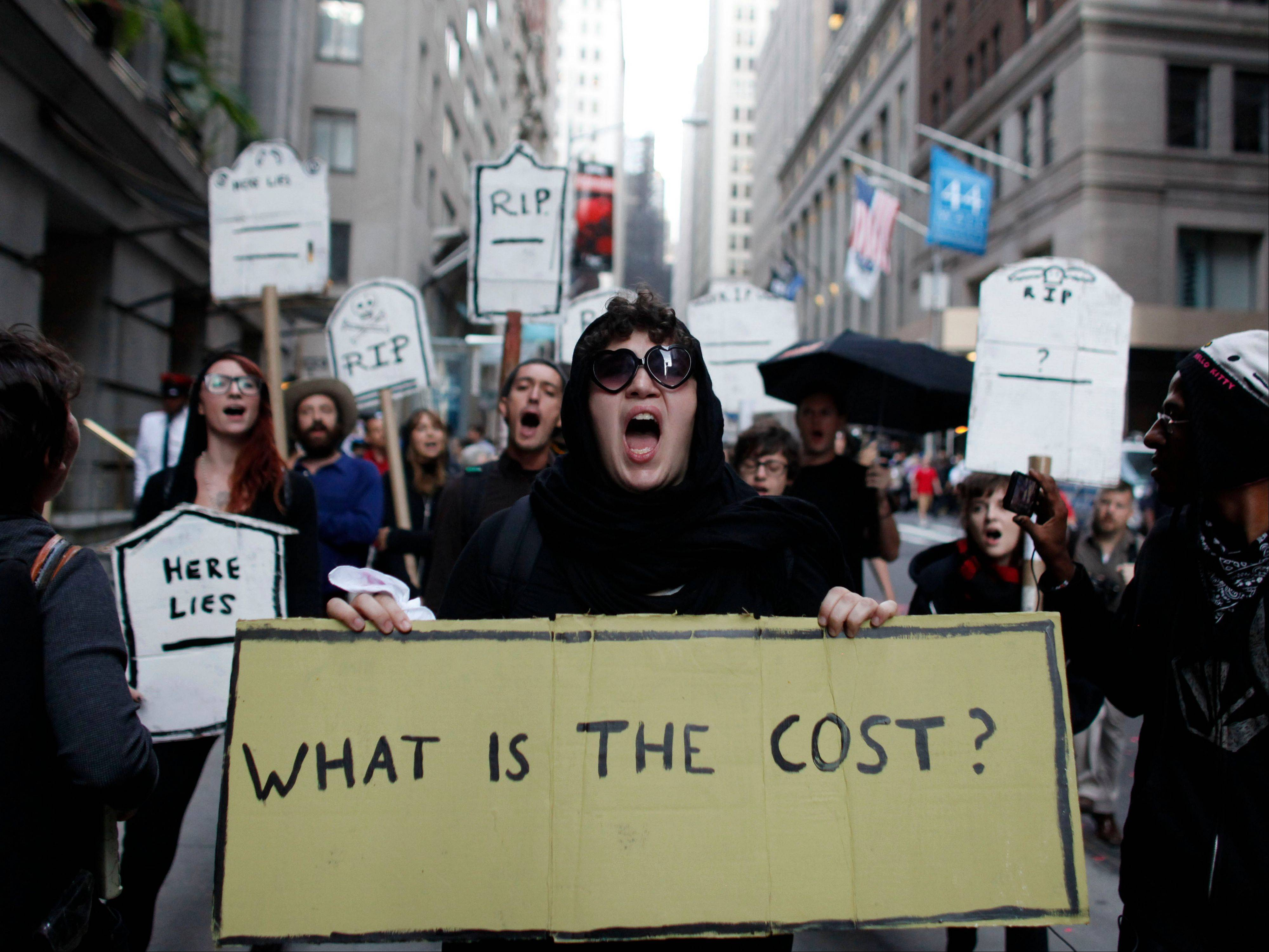 Protestors chant during an Occupy Wall Street march Monday in New York. About a dozen protestors were arrested Monday after sitting on the sidewalk.