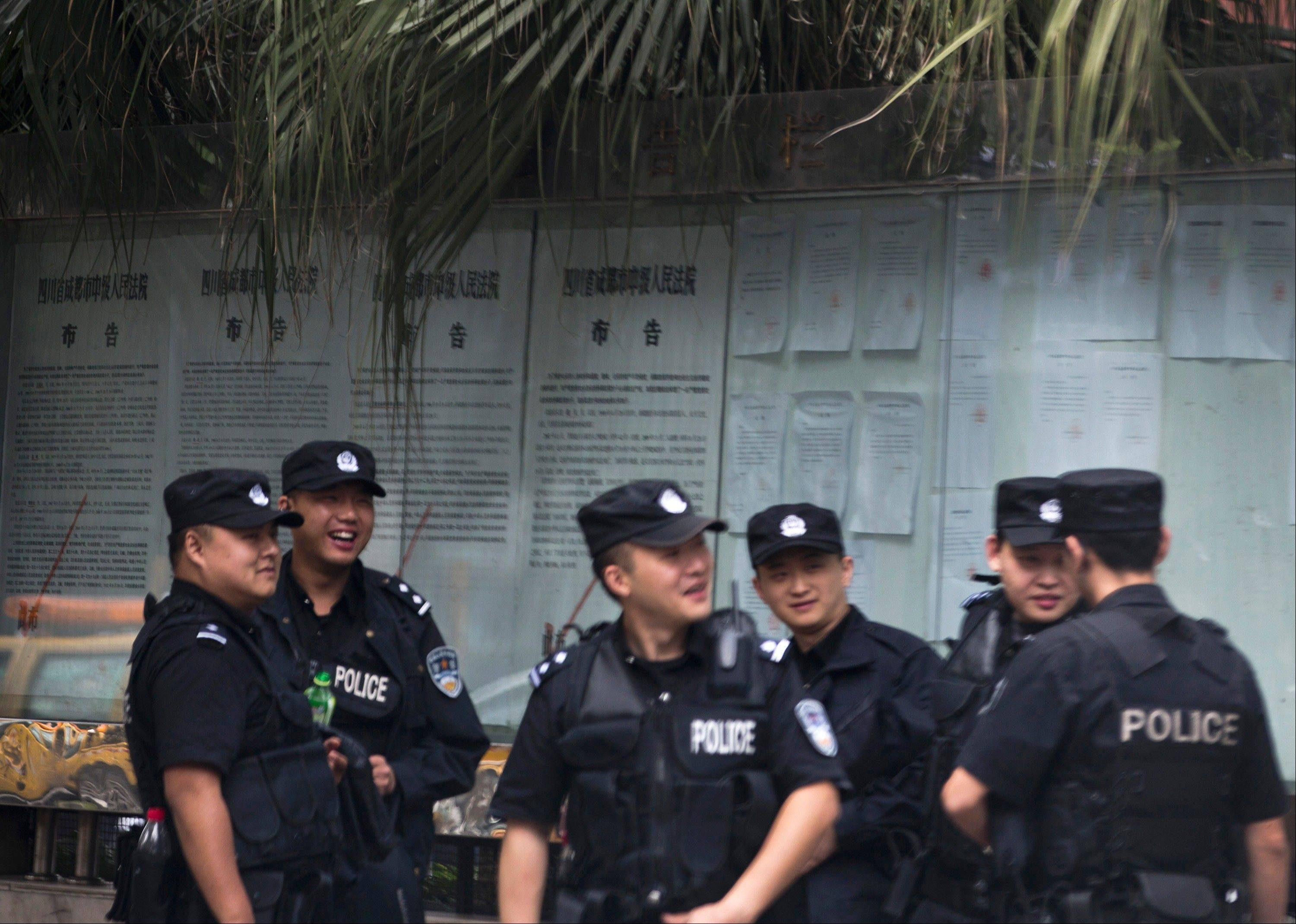 Chinese policemen huddle near the Chengdu Intermediate People�s Court, where Wang Lijun will be tried on Tuesday, in Chengdu in southwest China�s Sichuan province Monday. At the height of his career, Wang led a police crackdown on the violent underworld in a sprawling metropolis. Now the former police chief is in the hands of the opaque Chinese justice he once brandished against others.