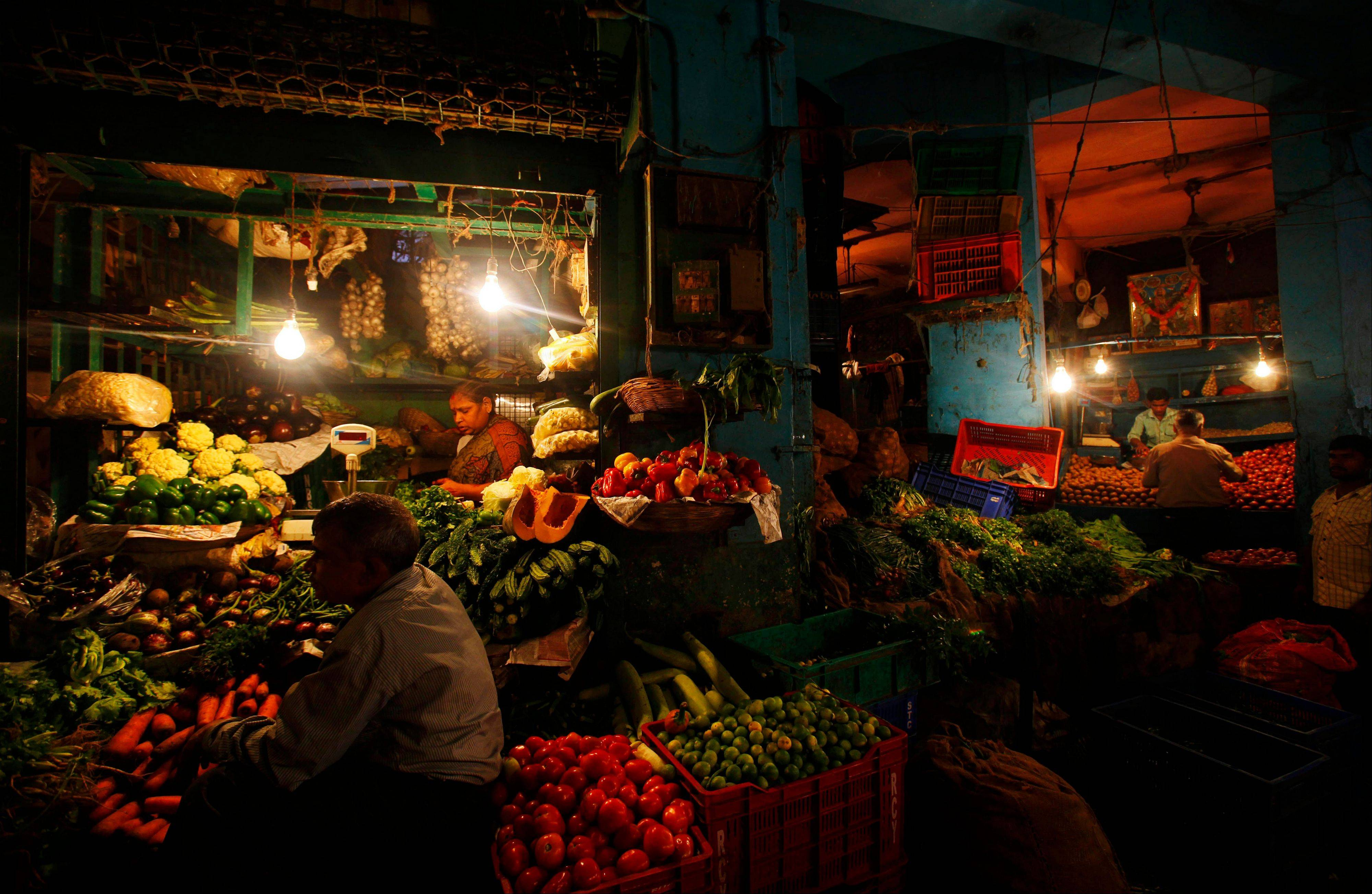 People shop at a vegetable market in Mumbai, India, Monday, Sept. 17, 2012. India's central bank, Reserve Bank of India, on Monday cut the cash reserve ratio as it tries to