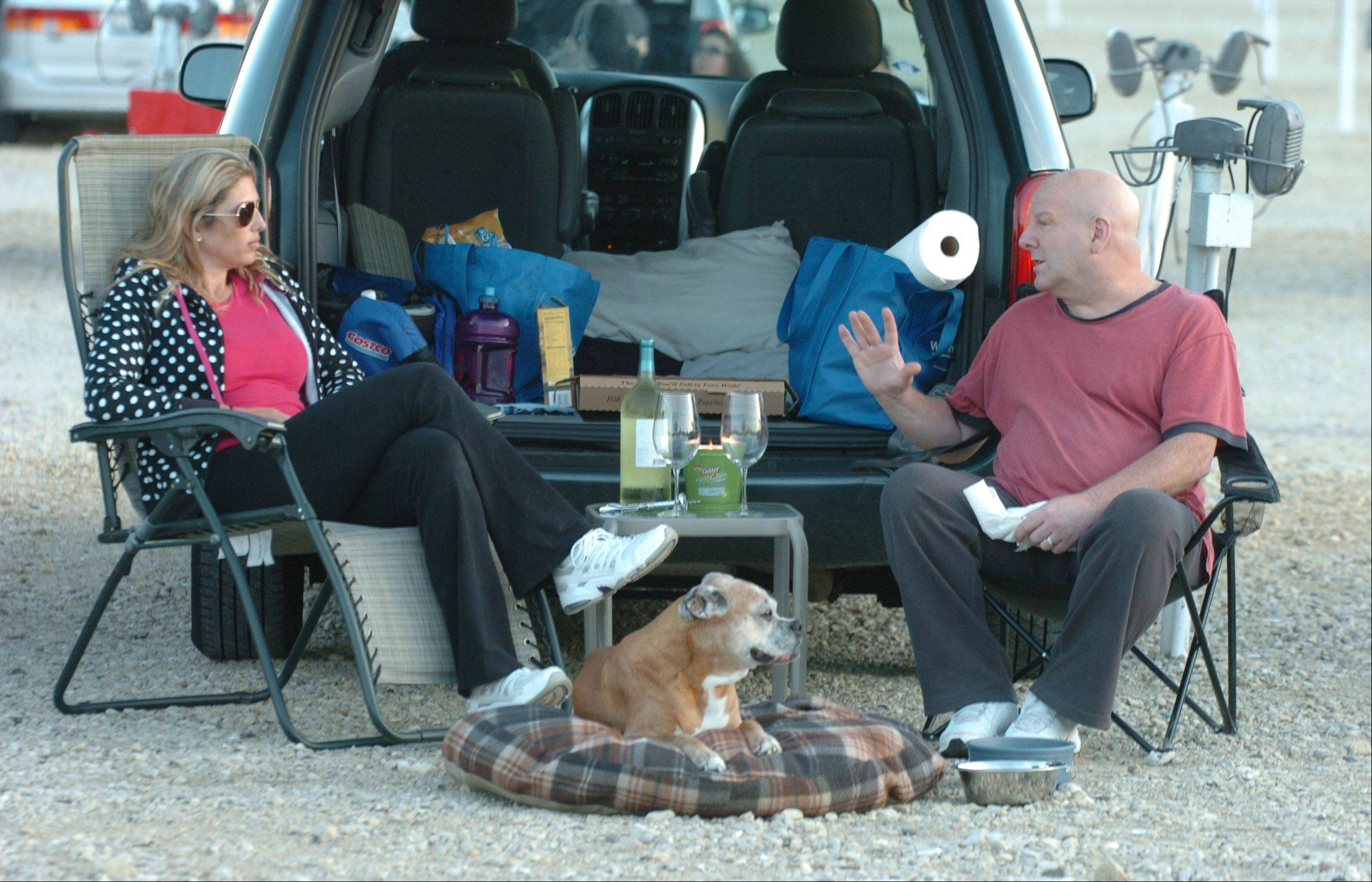 Greg and Lisa Schwartz of Carol Stream and their dog, Molly, prepare to enjoy the drive-in show with a pizza and a bottle of wine.