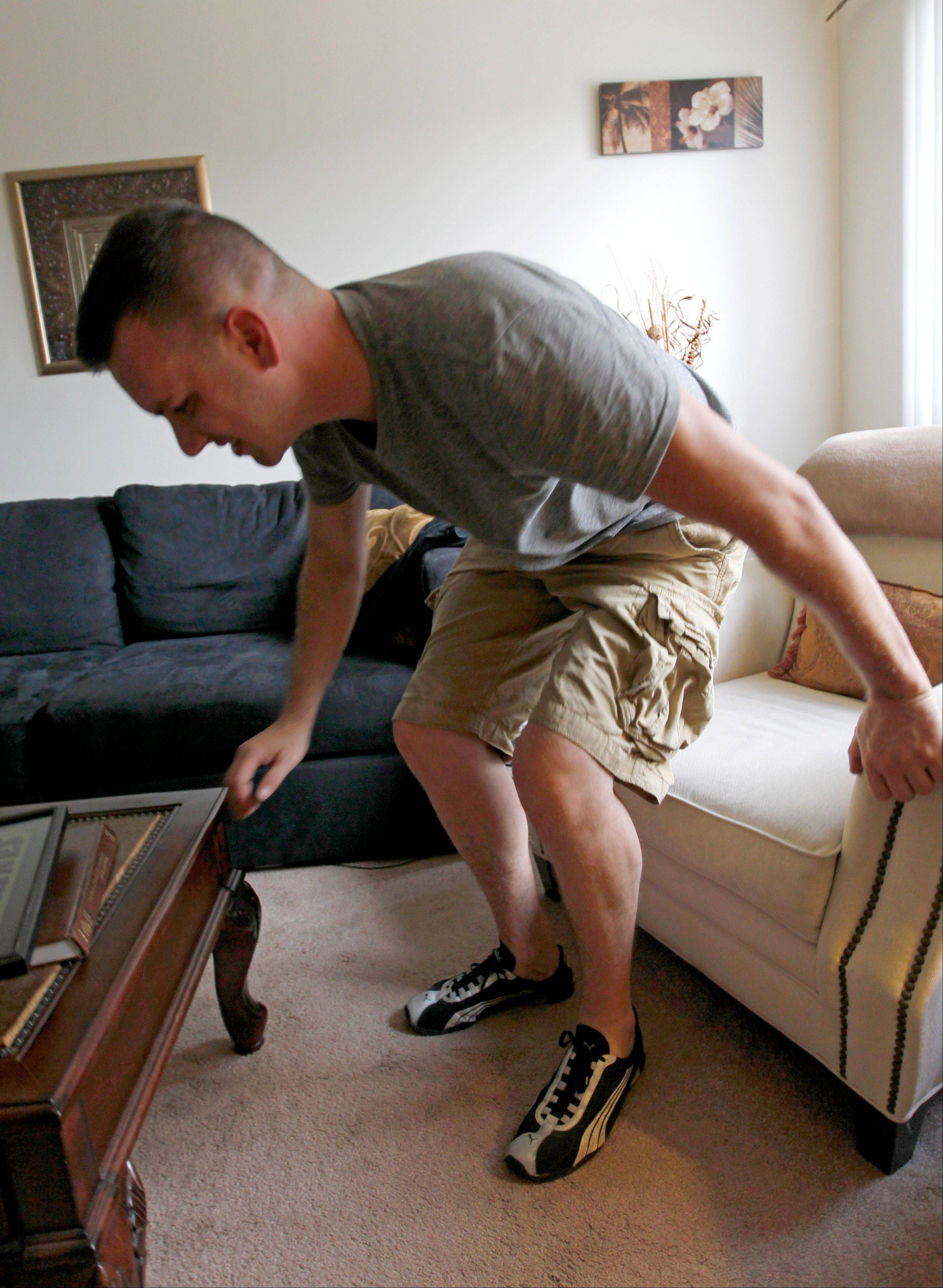 Marine Sgt. Ron Strang gets up from a chair in the living room of his home in Jefferson Hills, Pa. Strang has received an experimental implant of connective tissue developed from pigs.