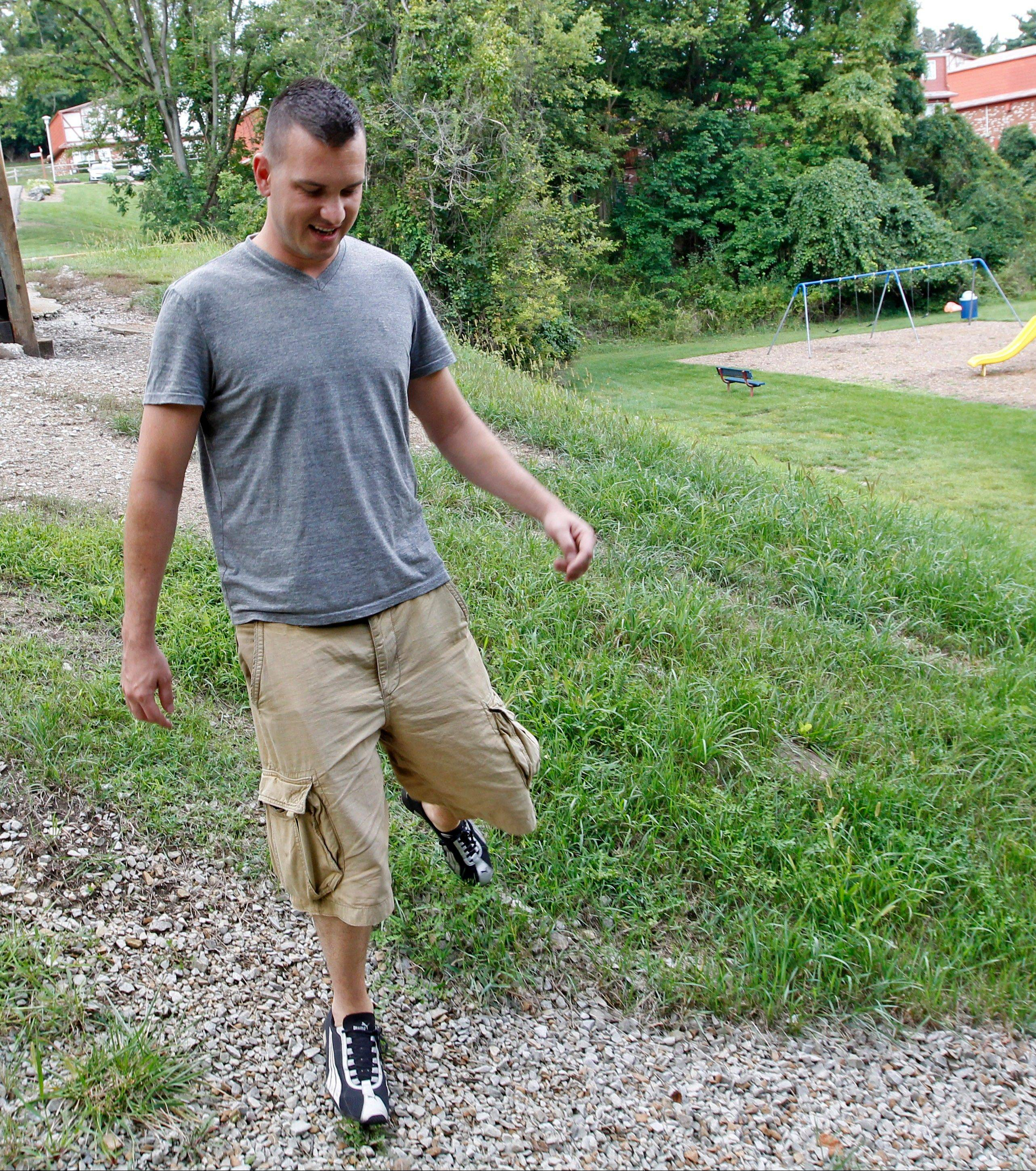 Marine Sgt. Ron Strang flexes the leg that was injured in a bomb blast in Afghanistan as he walks down a hill to a small park near his home in Jefferson Hills, Pa.