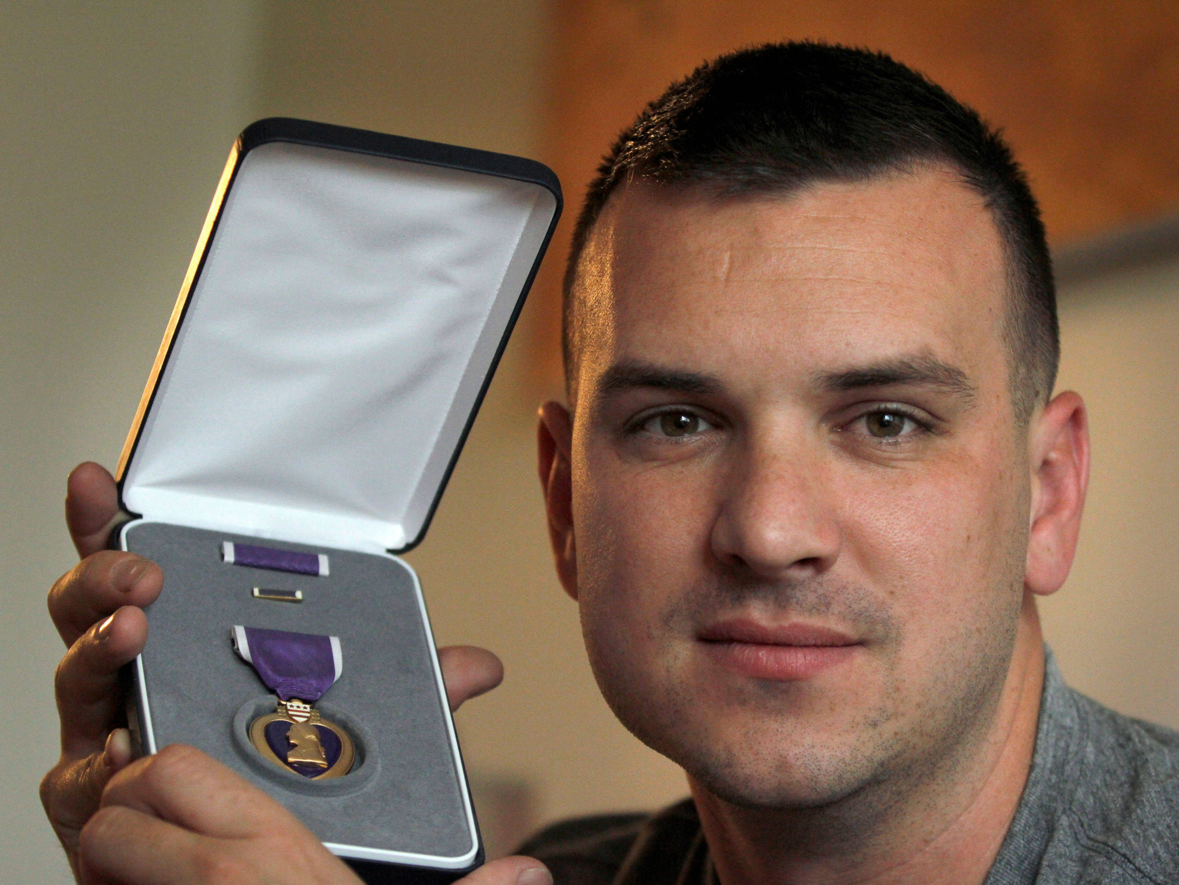 Marine Sgt. Ron Strang holds his Purple Heart medal in the living room of his home in Jefferson Hills, Pa. The 28-year-old former Marine sergeant lost half of a thigh muscle to shrapnel, leaving too little to stabilize his gait.