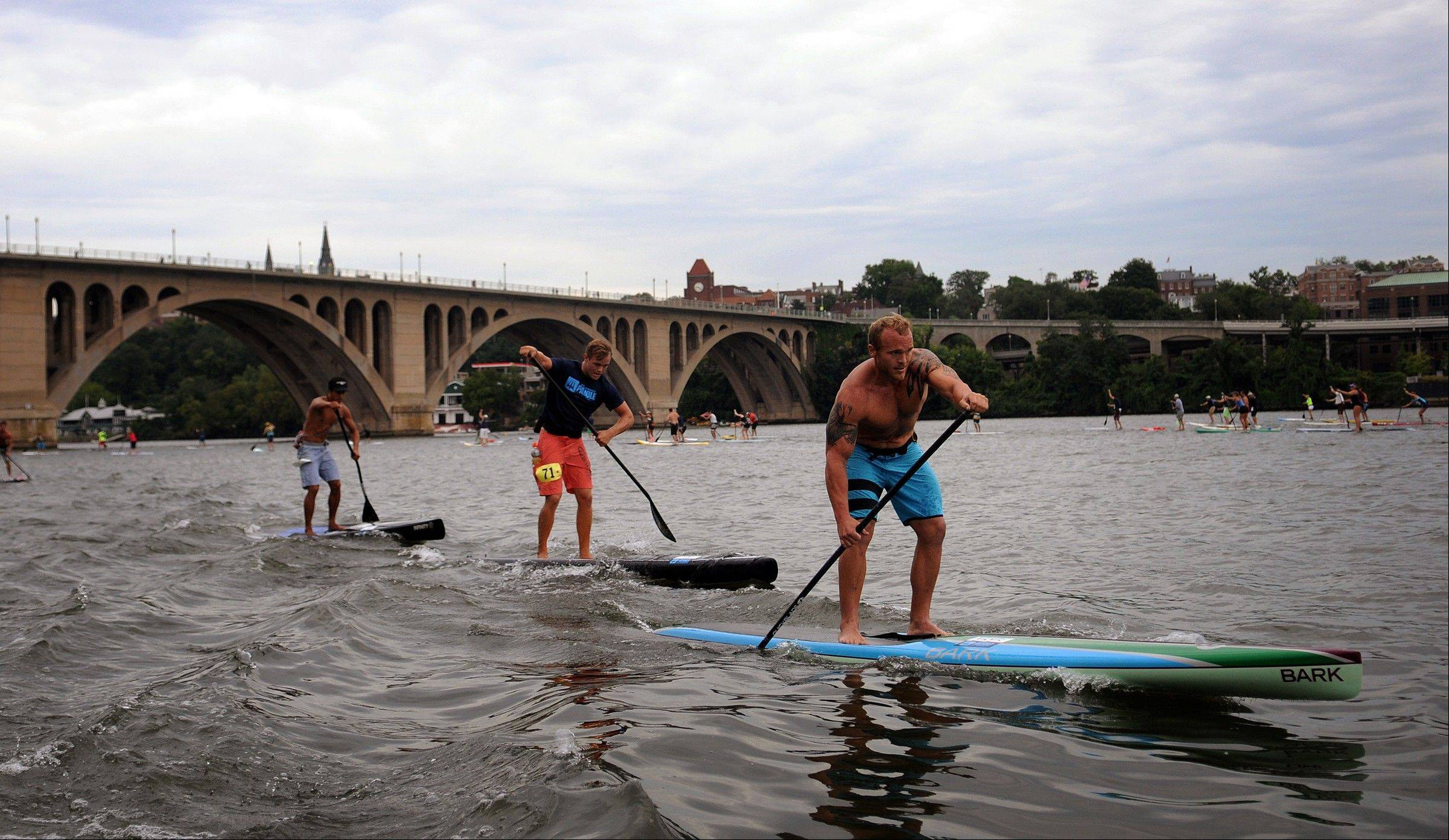 Christopher Johnson of North Carolina takes the lead during the Waterman's Paddle for Humanity competition on the Potomac River in Washington, D.C.