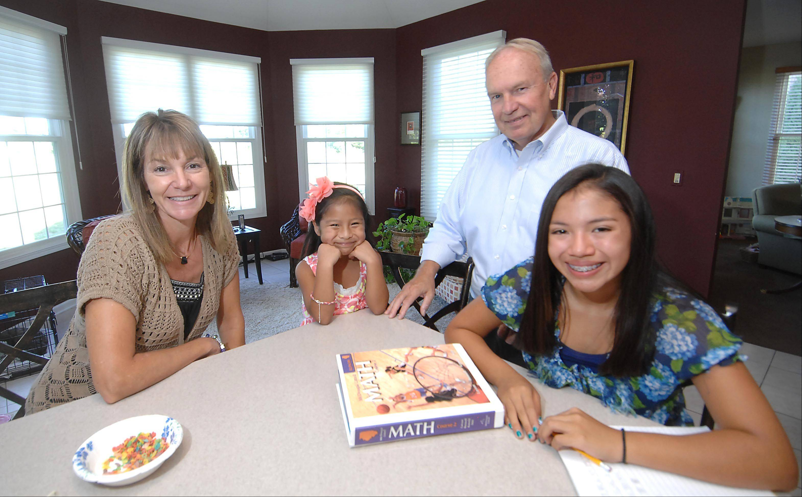Russ and Leeann Schweizer with their adopted Guatemalan children Ysabel and Gabriela, right, in their Lakewood home. Russ recently returned from a trip with Living Water International to drill a well in Guatemala.