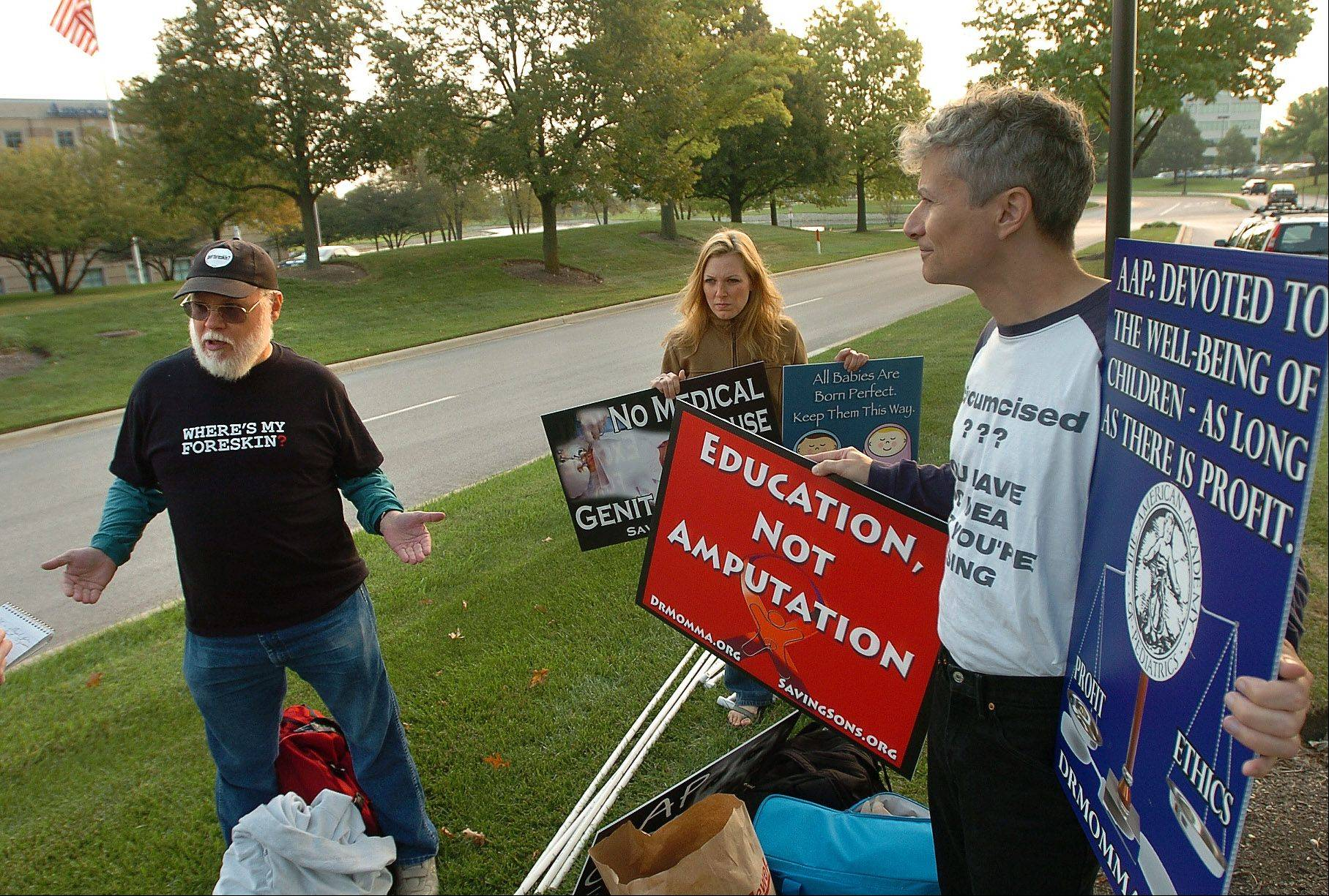 From left, Dan Strandjord, Erica Wijenayaka and Ron Low, were among a group protesting the American Academy of Pediatrics' stance on circumcision at the association's Elk Grove Village headquarters Monday morning.