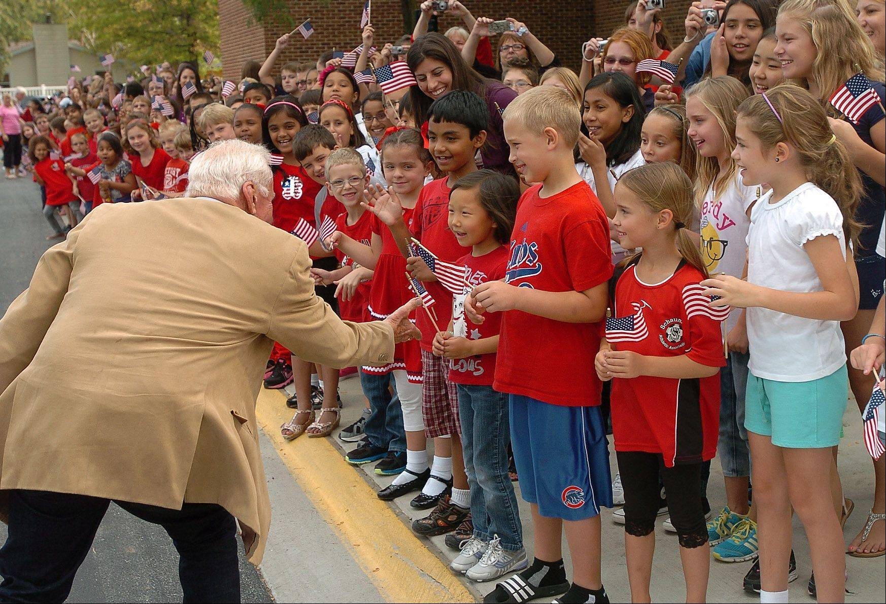 Astronaut Buzz Aldrin greets students upon his arrival Monday at the Schaumburg elementary school named after him in 1971. Aldrin told students they can help achieve feats even greater than his 1969 moon landing.
