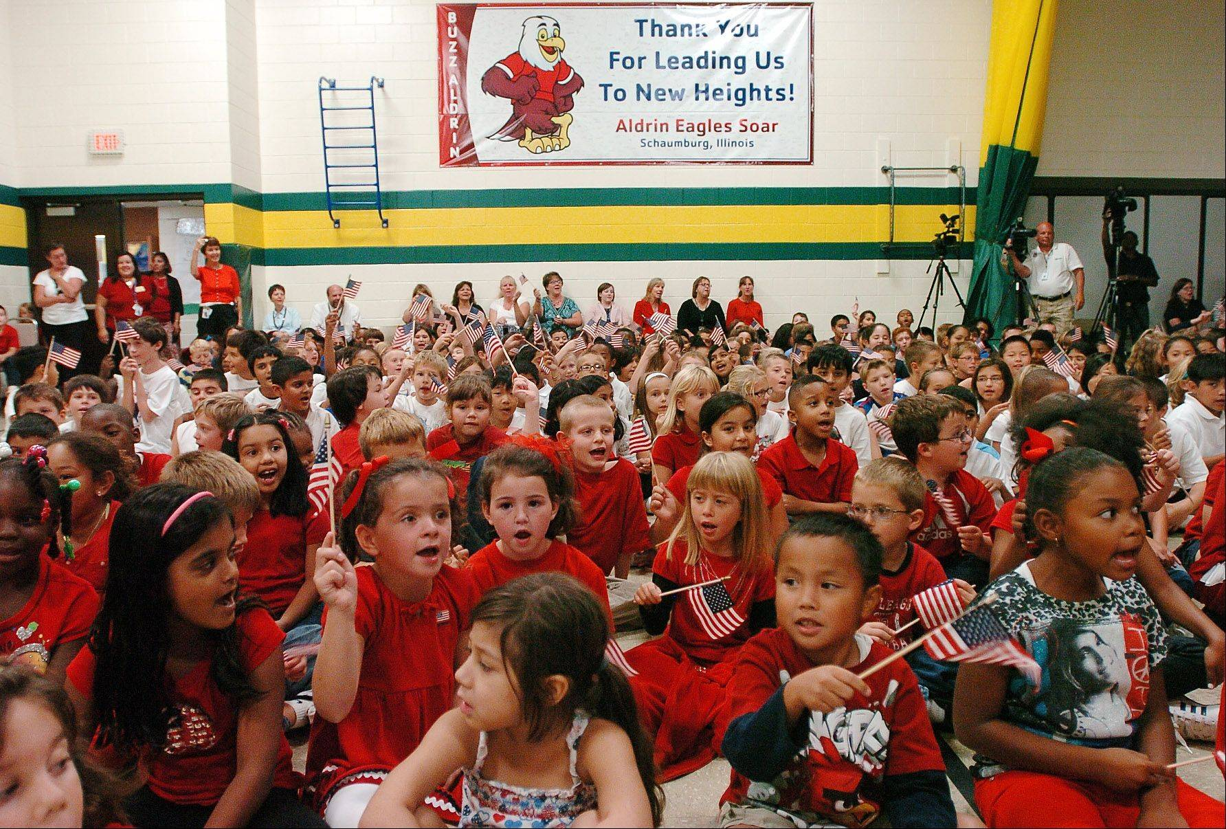 "Students sing ""It's a Grand Old Flag"" to astronaut Buzz Aldrin at Aldrin Elementary School in Schaumburg Monday afternoon."