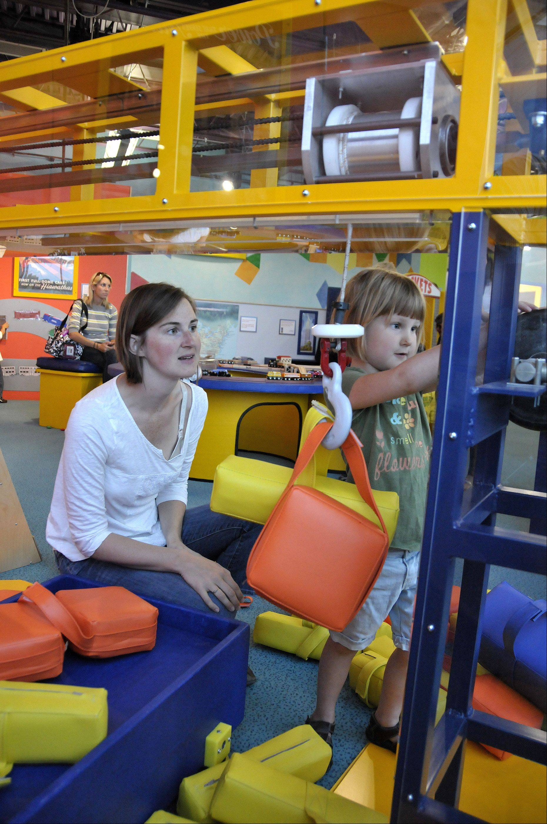 Patricia Mackie of Bolingbrook watches as her daughter, Delilah, works the crane at the DuPage Children's Museum to load luggage and freight.