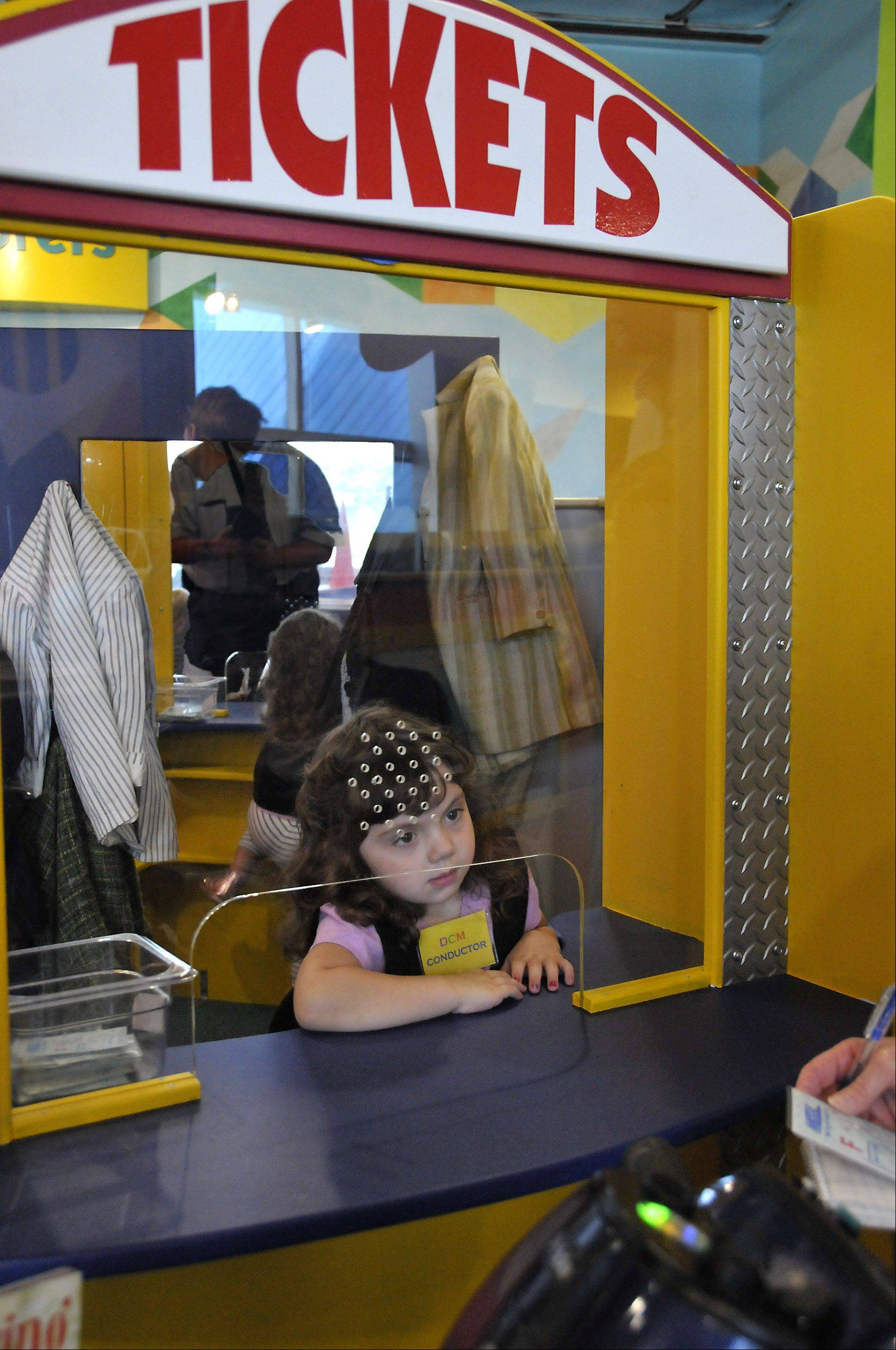 Celia Jefferson, 4, of Evanston, minds the ticket booth at the DuPage Children's Museum's train exhibit. Her family members are regulars at the Naperville museum.