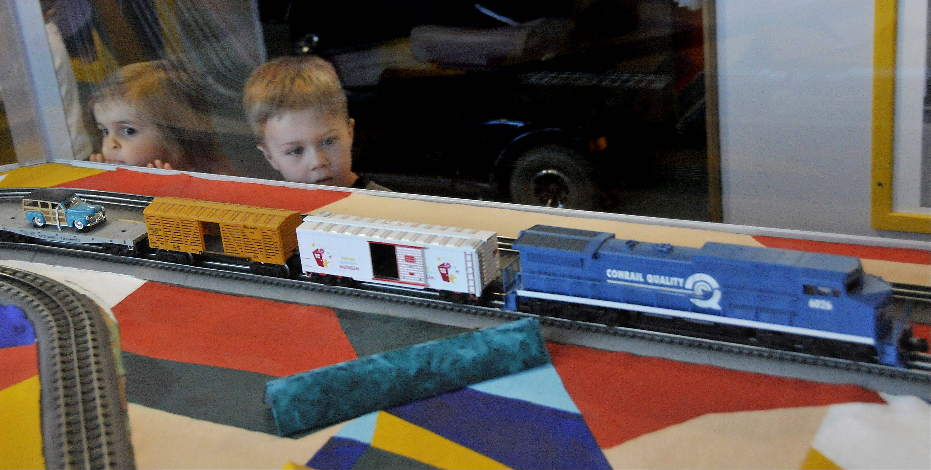 Kids watch the trains go around in the revamped electric model train exhibit that features colorful shapes instead of the traditional, scenic layout at the DuPage Children's Museum in Naperville.