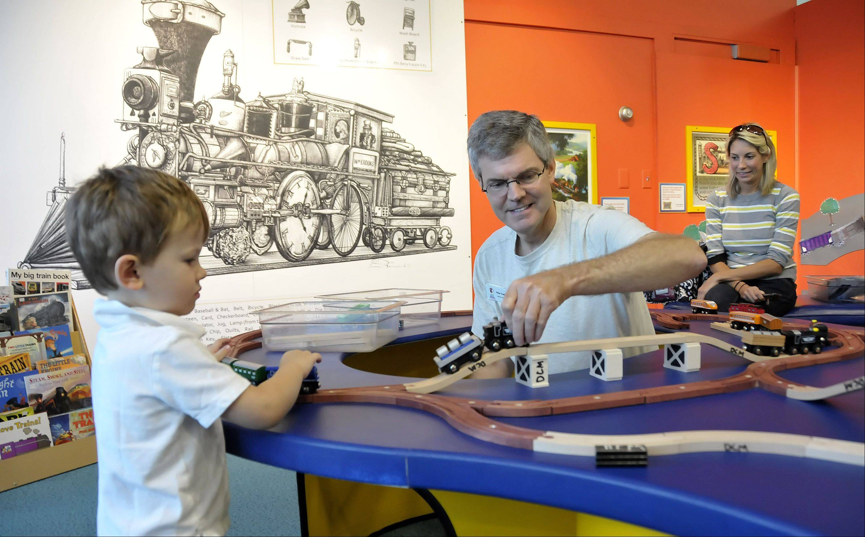 DuPage Children's Museum exhibit director Peter Crabb, center, demonstrates one of the wooden trains for James Duncan, 2. The wooden trains that kids can push around the tracks are a new part of the updated exhibit.