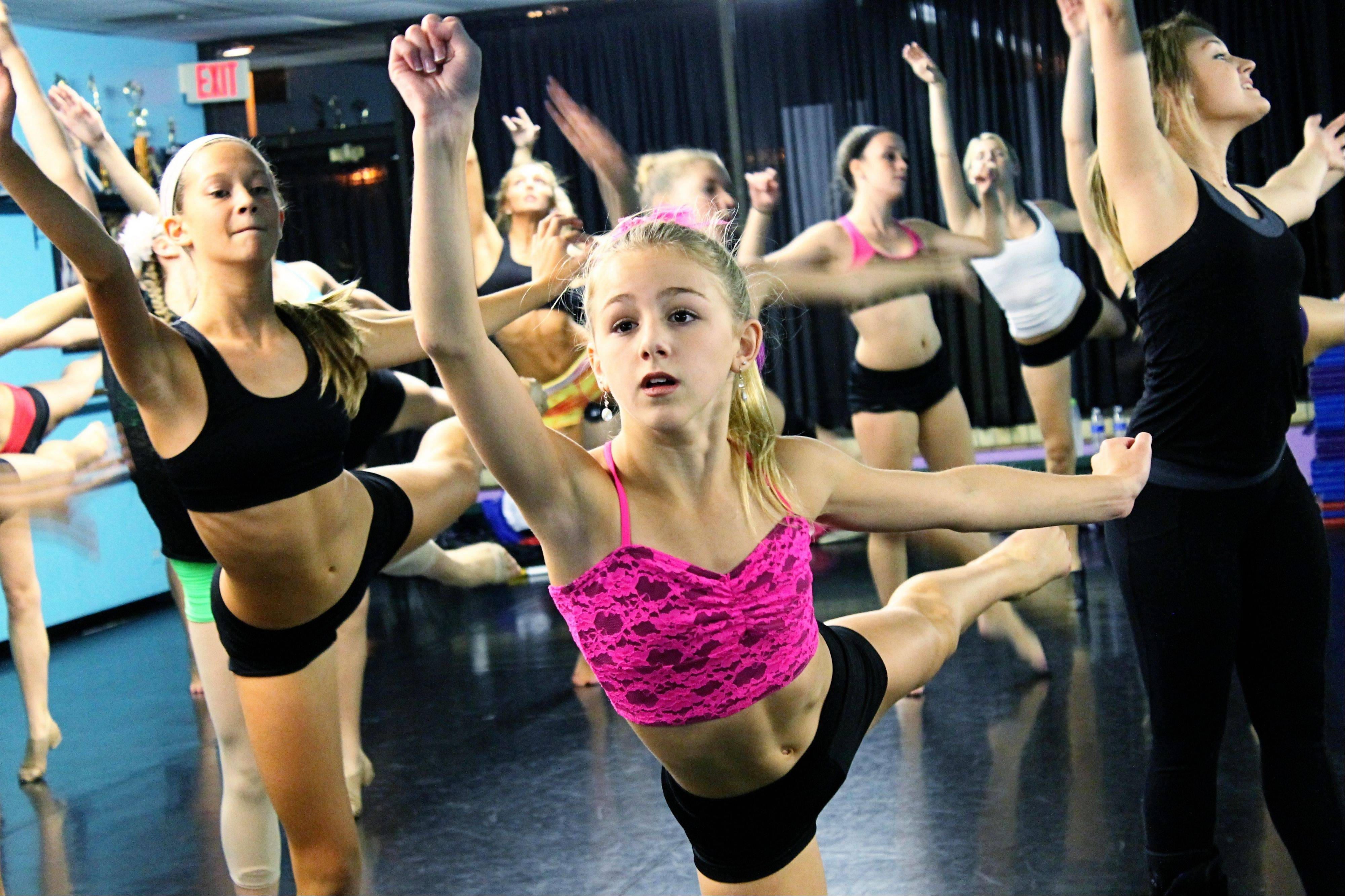"Chloe Lukasiak, center, from the Lifetime reality TV show ""Dance Moms"" dances with her choreographer Brittany Pent, far right, and local dance students at the Dance Project dance studio in Hoffman Estates. Chloe and her mother, Christi, visited the studio on Saturday."