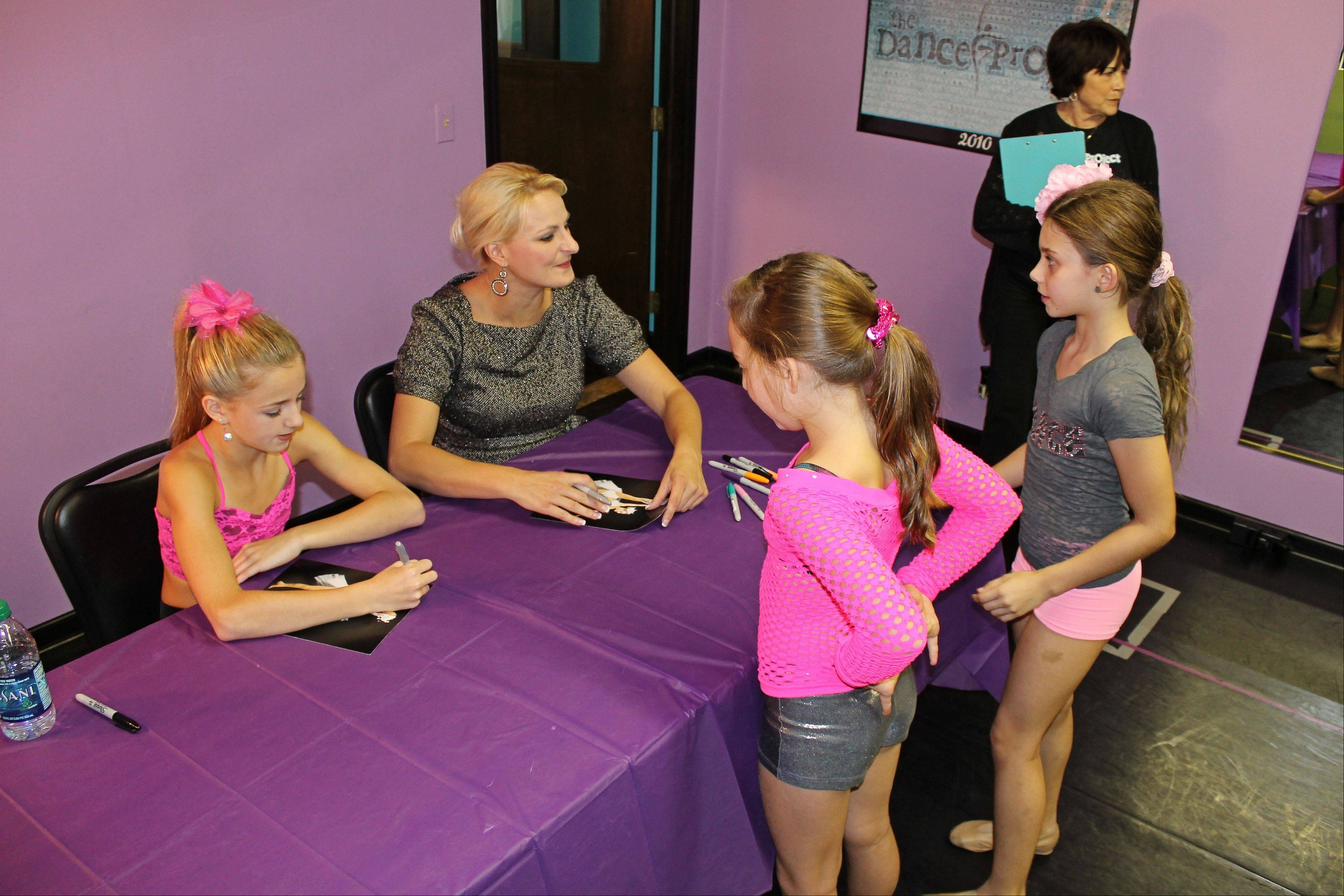 "Chloe Lukasiak, left, and her mom, Christi, from Lifetime's reality TV show ""Dance Moms"" autograph pictures for students at the Dance Project dance studio in Hoffman Estates. The mother-daughter duo visited the studio Saturday."