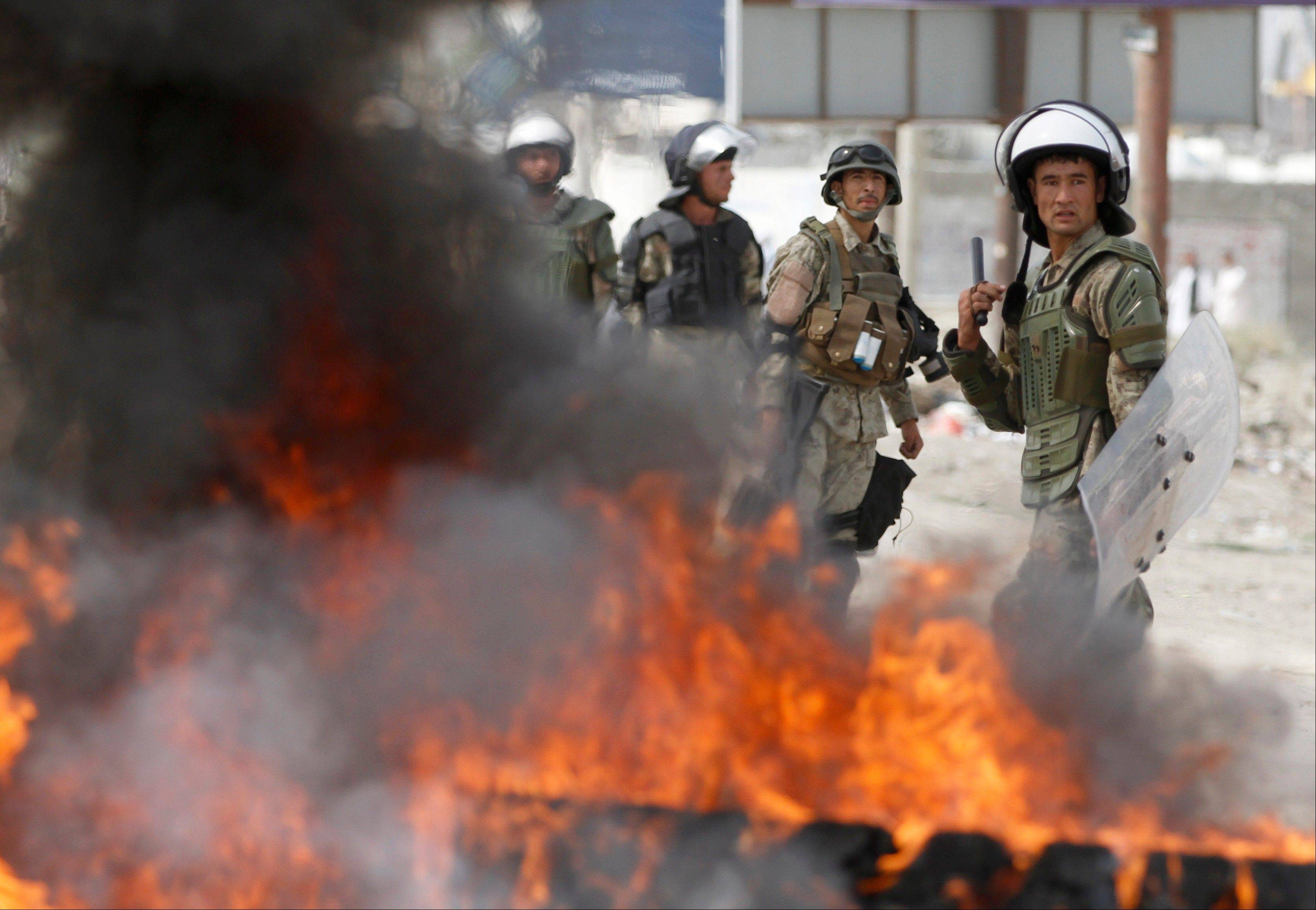 Afghan police stand by burning tires during a protest Monday in Kabul, Afghanistan. Hundreds of Afghans burned cars and threw rocks at a U.S. military base as a demonstration against an anti-Islam film that ridicules the Prophet Muhammad turned violent in the Afghan capital early Monday.