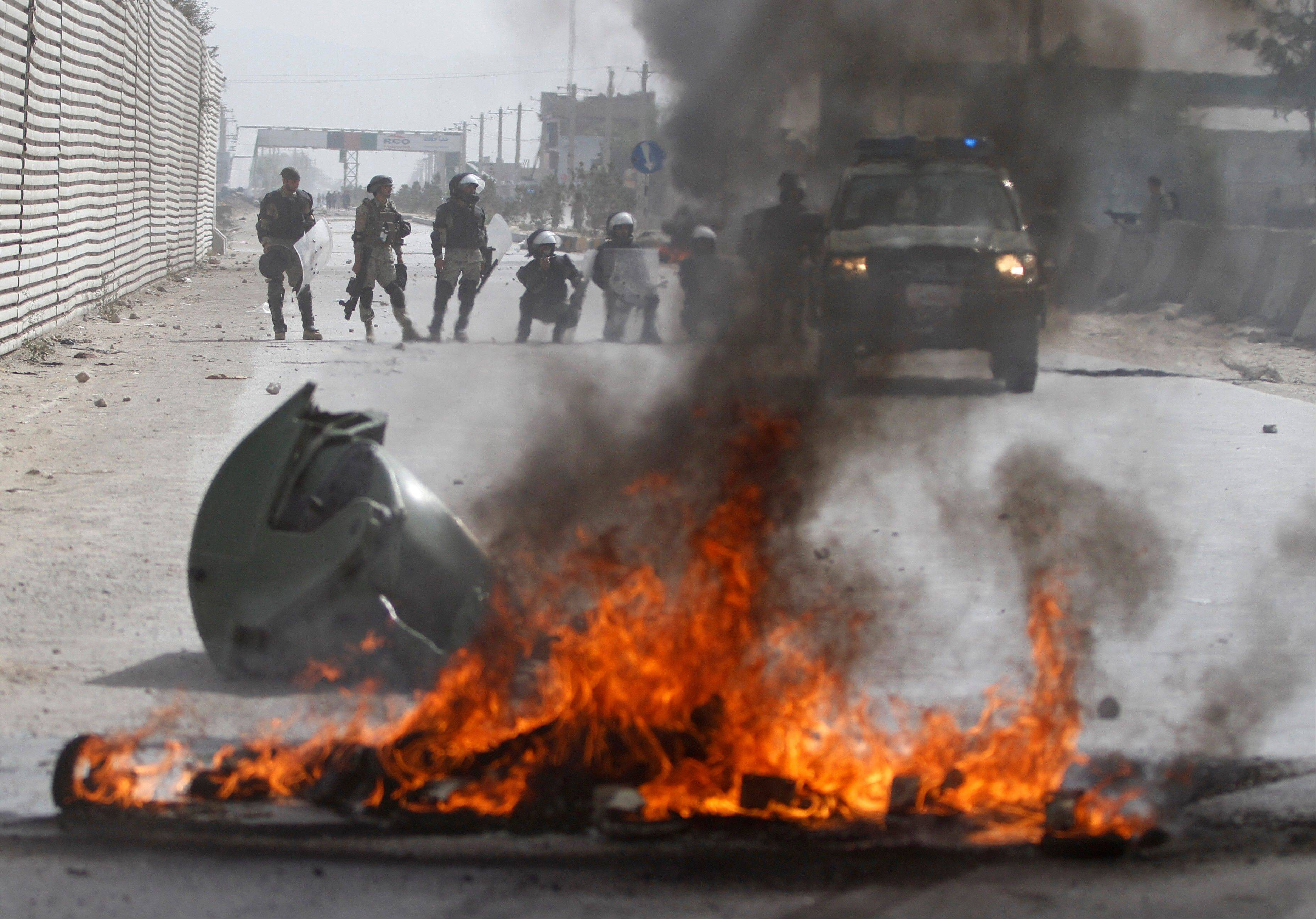 Afghan police stand by burning tires during a protest, in Kabul, Afghanistan, Monday.