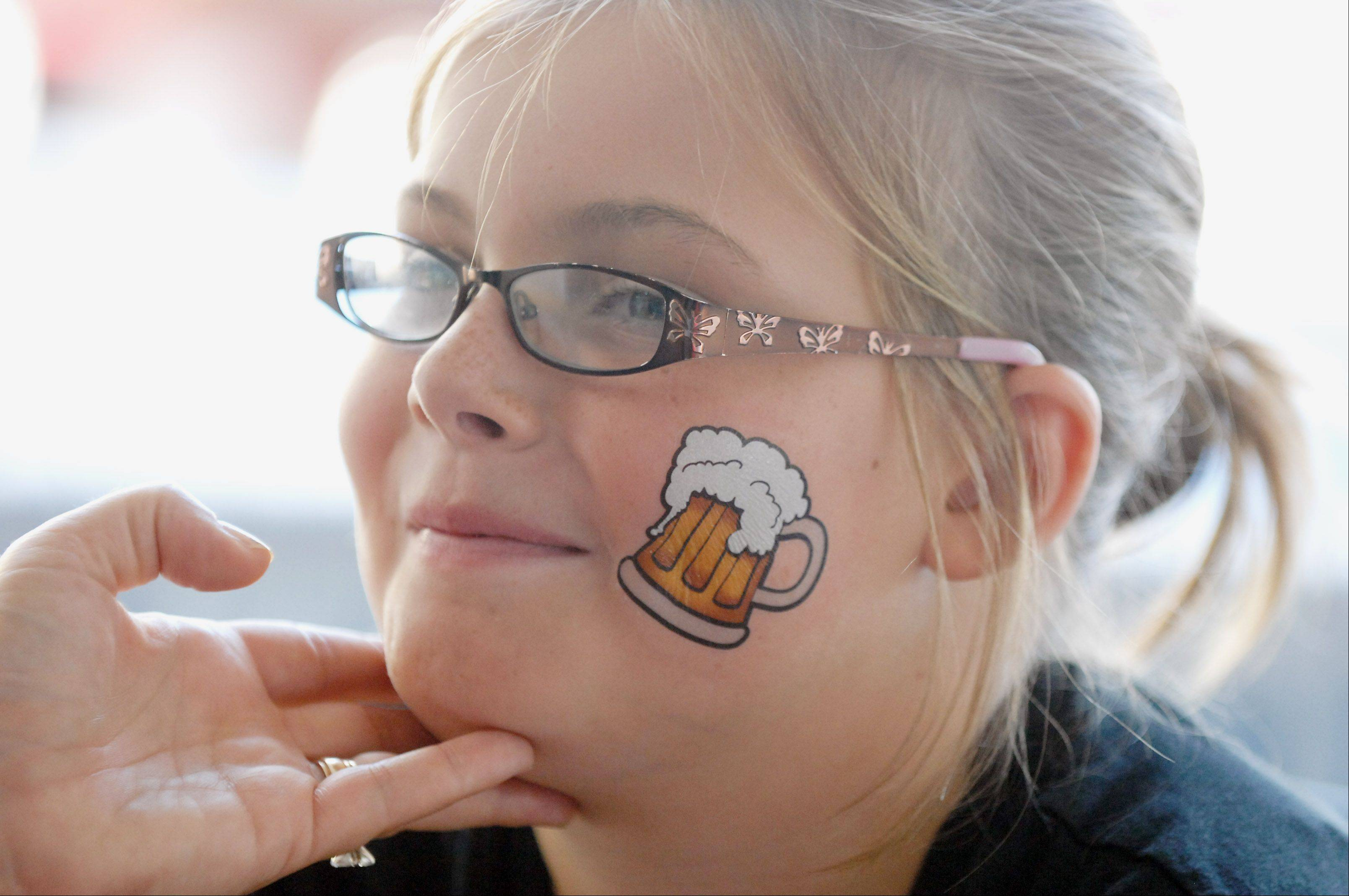 Molly Leno, 9, of Arlington Heights sports a beer tattoo during Oktoberfest in Itasca Saturday. The fest runs thorough Sunday and offers food, beer, and fun for all ages.