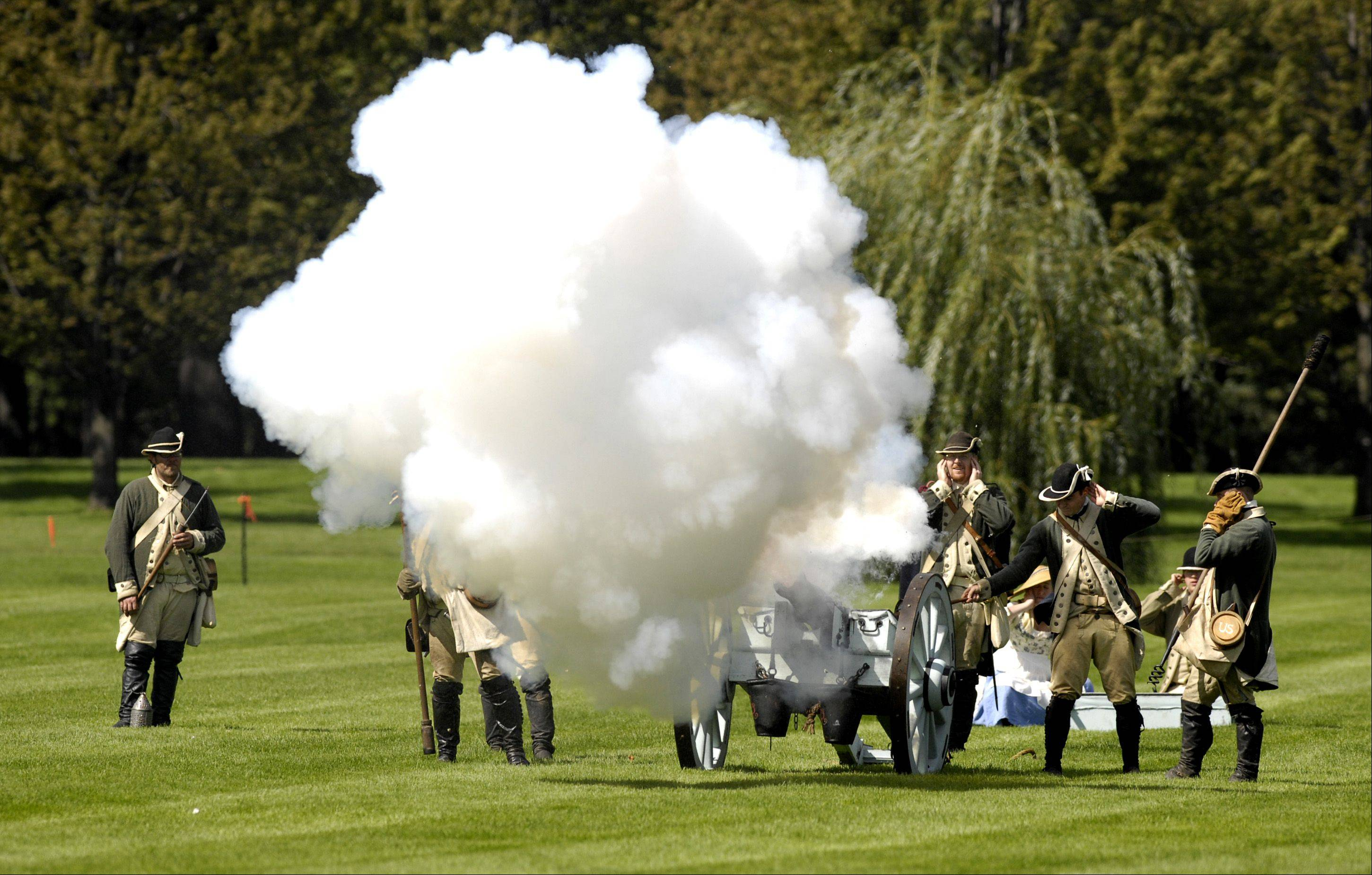 The Continental Army fires a canon during a Revolutionary War battle re-enactment at Cantigny Park in Wheaton, Sunday.