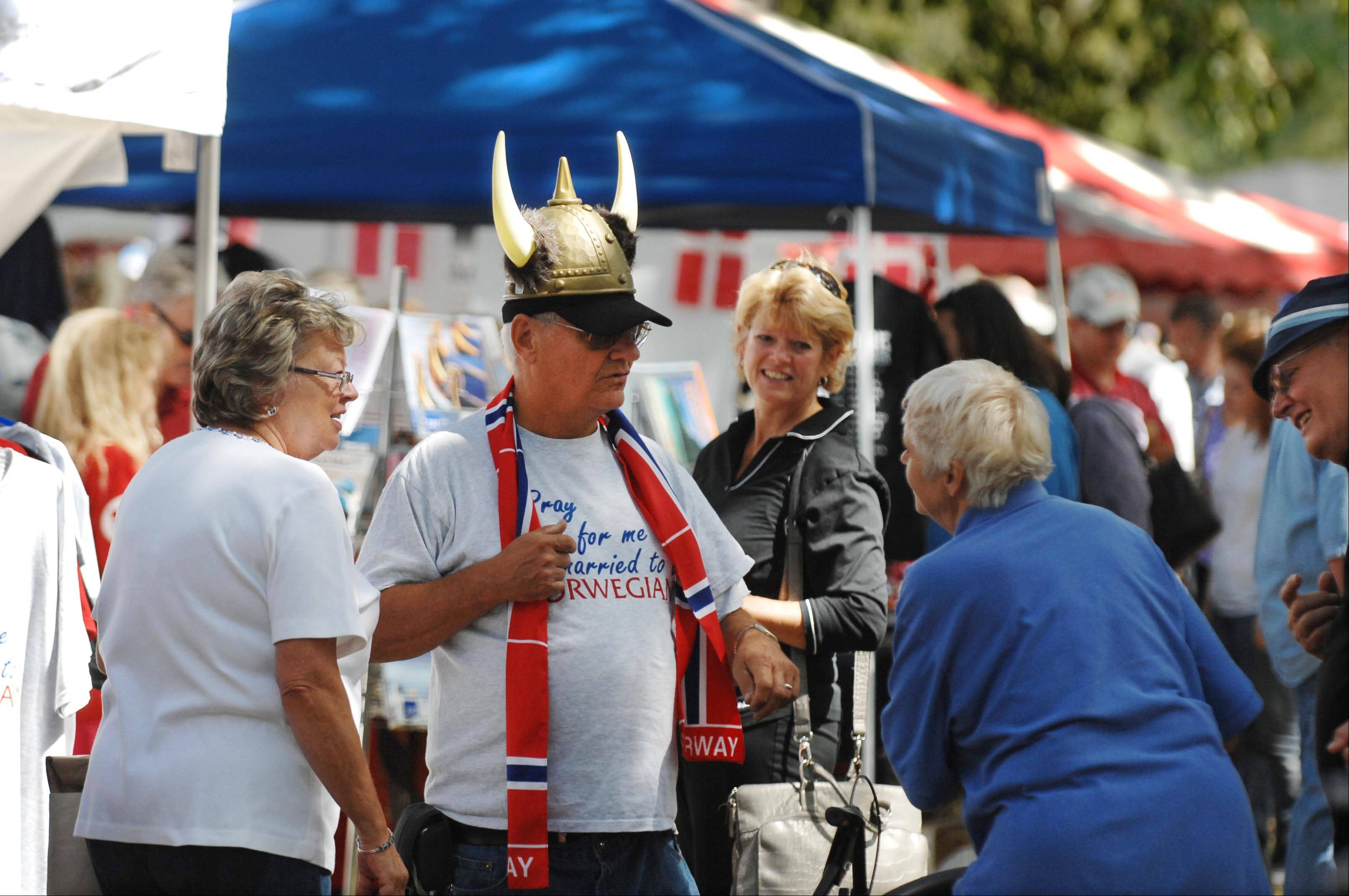 Wearing Viking headgear, Lane Backus shows off his Norwegian scarf to visitors of his retail booth, Lena & Ole's Gifts, Sunday at the 33rd Annual Scandinavian Day Festival at Vasa Park in South Elgin. He and his wife are from Wisconsin and she is Norwegian.