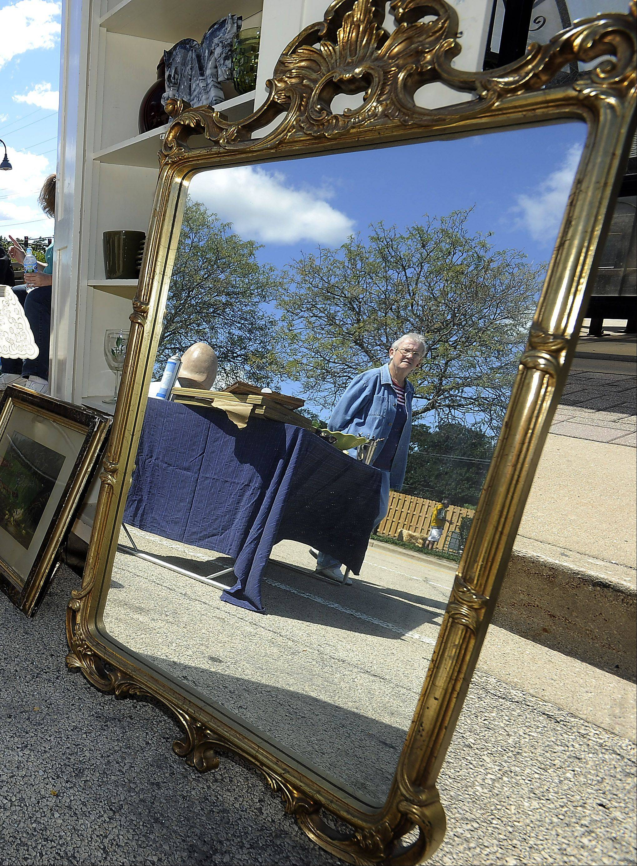 Dolores Menier of Wood Dale checks out the garage sale of items including this mirror at the Bartlett Heritage Days festival on Saturday.