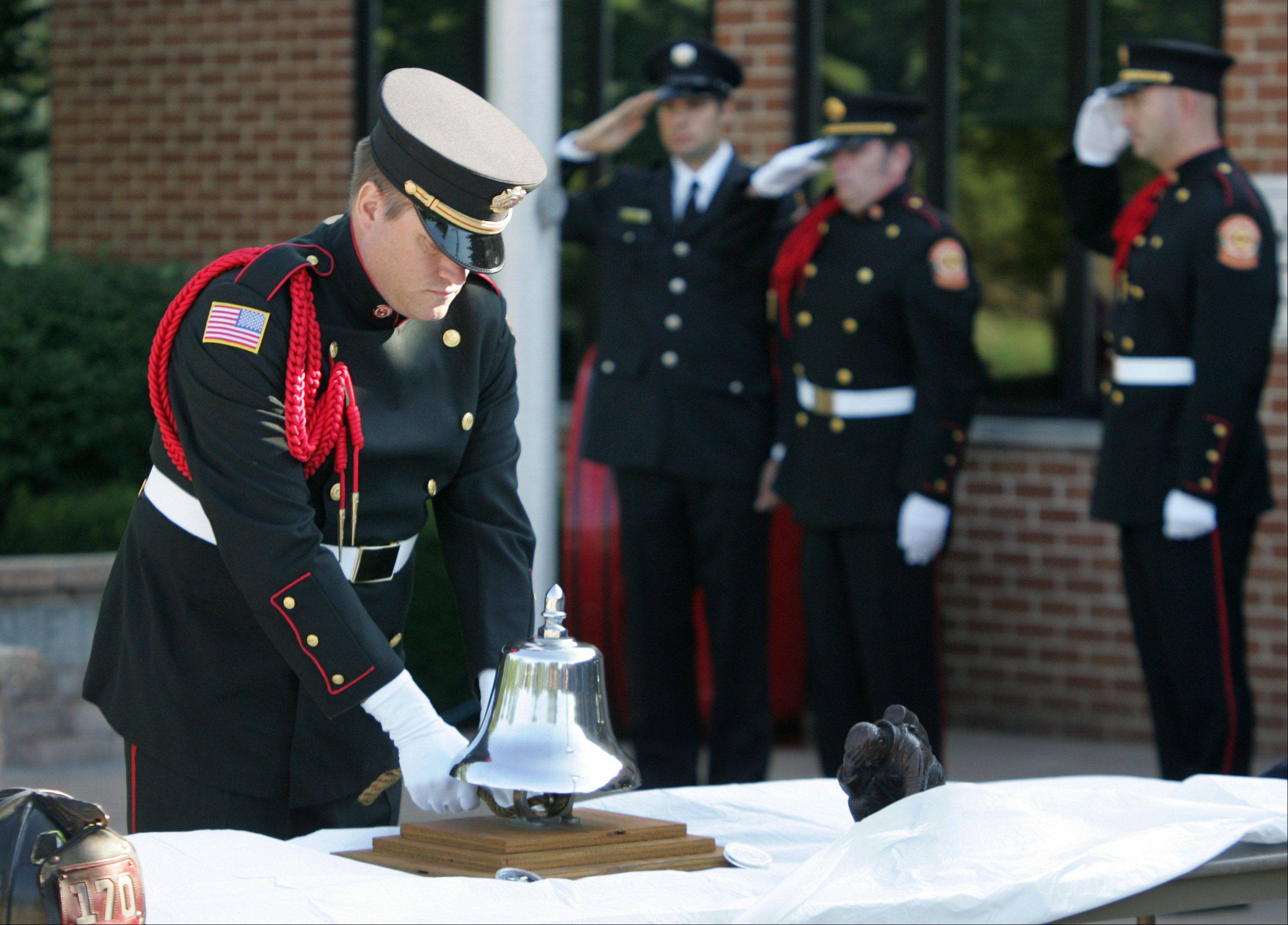 Firefighter Jim Cook rings the bell during the Remember 9-1-1 Ceremony by the Lincolnshire-Riverwoods Fire Protection District Tuesday at the fire station on Schelter Road.