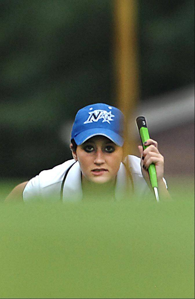 Ariana Furrie of St. Charles North lines up her putt on the last green Monday at the Elgin Country Club girls golf invitational.